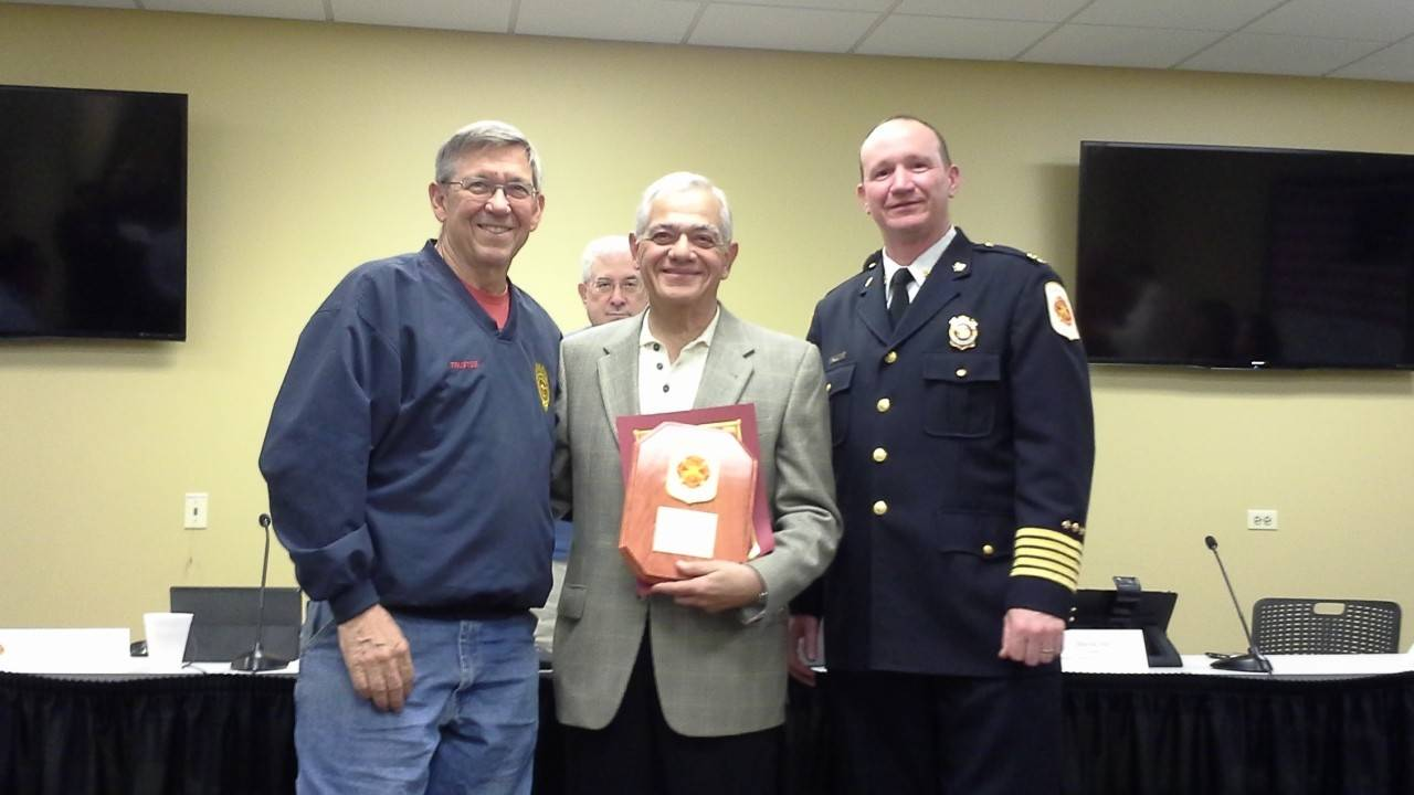 Barrington resident Frank Cantafio (center) posing with the plaque given to him by Countryside Fire Protection District board President Tom Rowan (left) and fire Chief Jeff Swanson (right) at the board of trustees' meeting Monday.