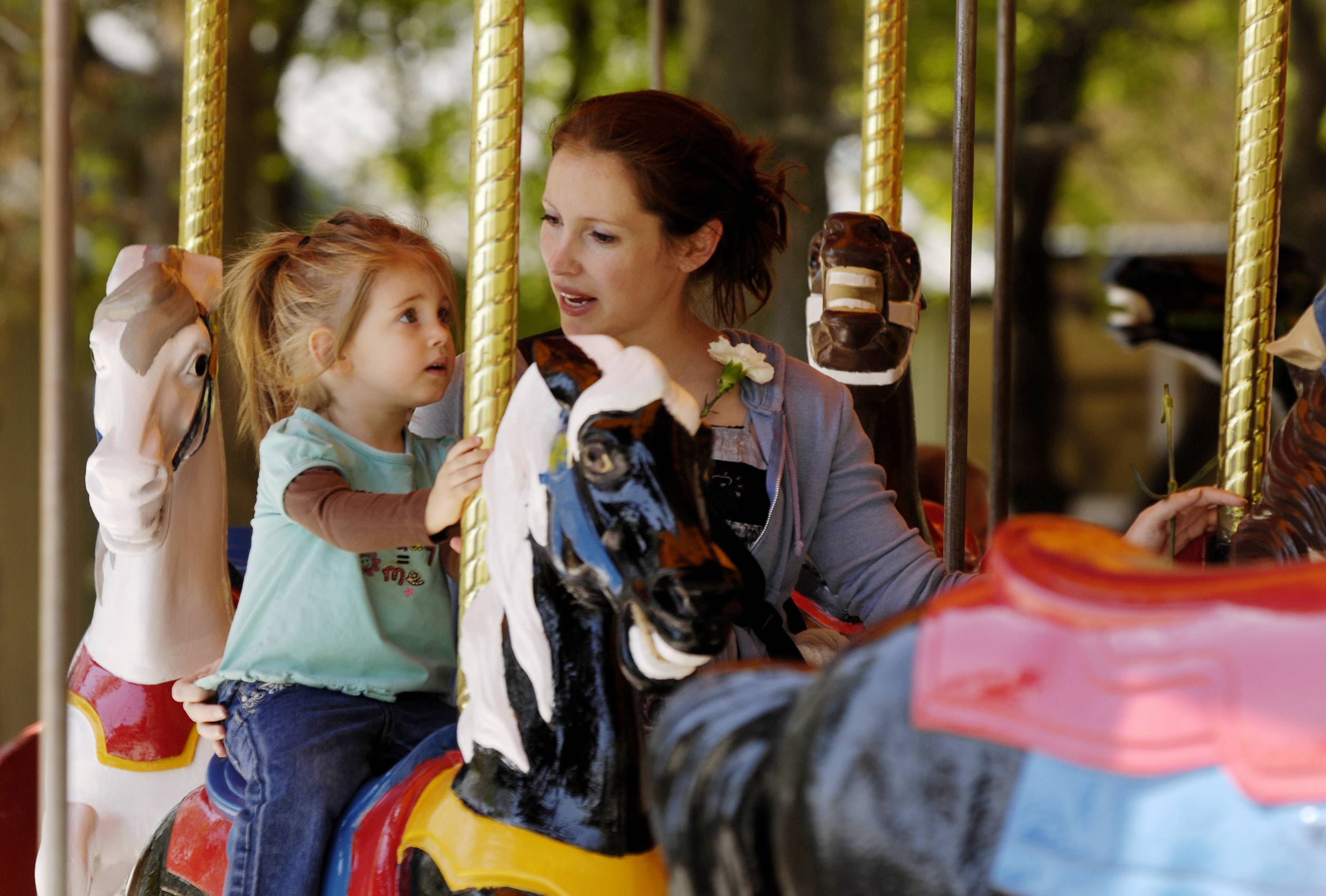 Josephine, 2 and Theresa Welsch of Aurora ride the carousel at Blackberry Farm in Aurora. The park opens for the season Thursday, May 1.