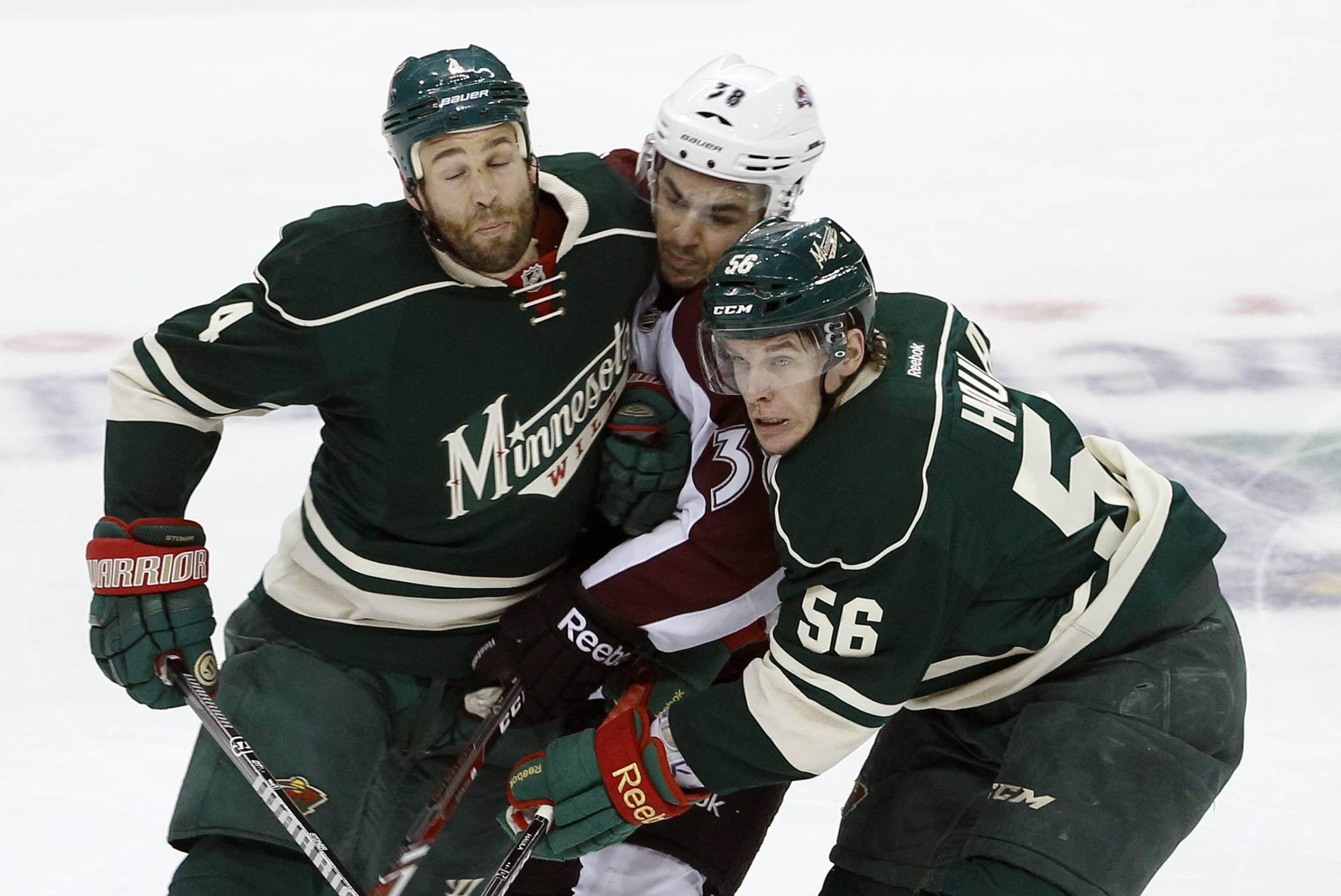 Colorado Avalanche center Joey Hishon is sandwiched between Minnesota Wild defenseman Clayton Stoner, left, and left wing Erik Haula (56), of Finland, during the first period of Game 4 of an NHL hockey first-round playoff series in St. Paul, Minn., Thursday, April 24, 2014. (AP Photo/Ann Heisenfelt)