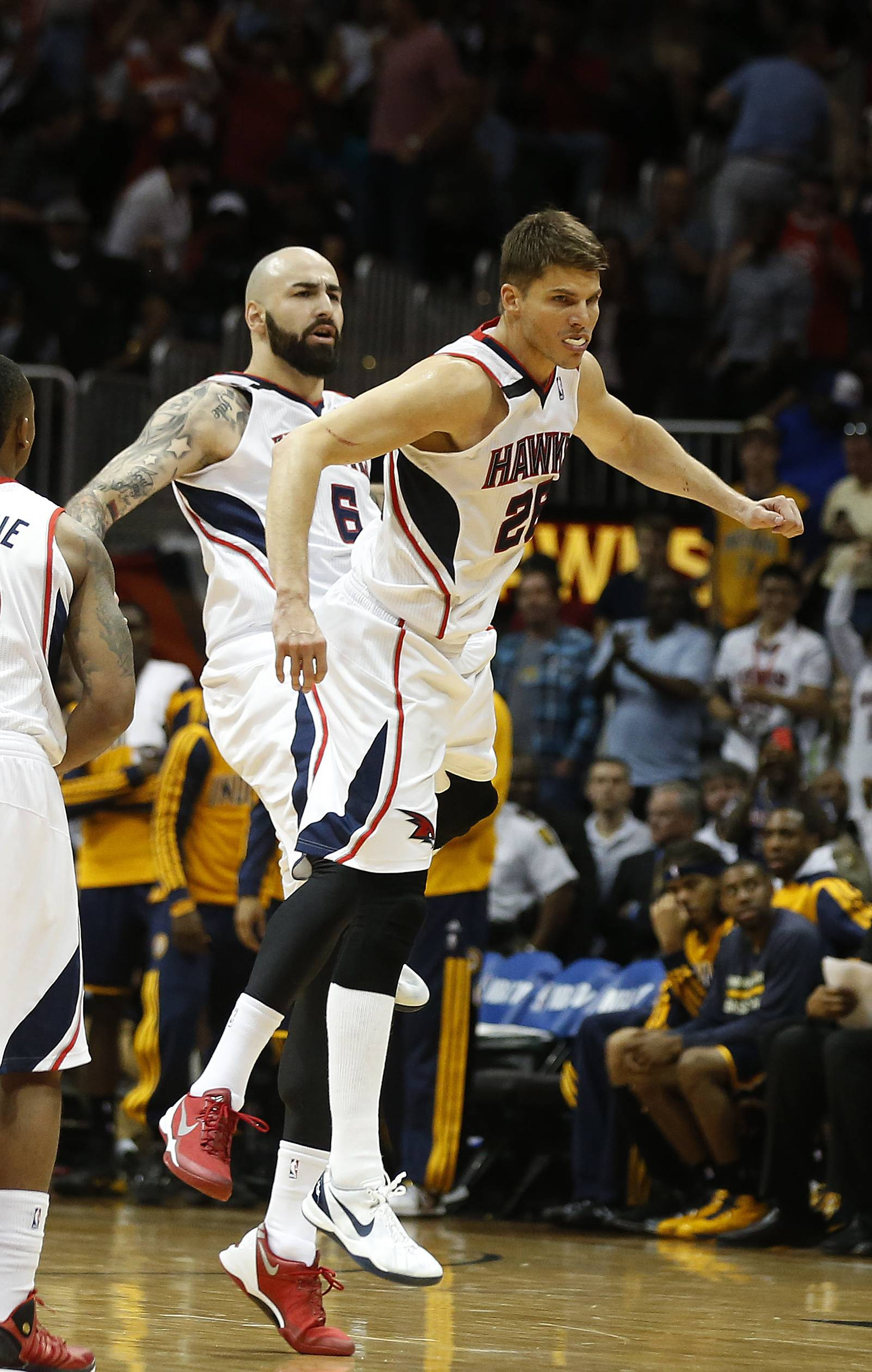 Atlanta Hawks guard Kyle Korver (26) celebrates with center Pero Antic, left, celebrate after hitting a three-point basket in the second half of Game 3 of an NBA basketball first-round playoff series against the Indiana Pacers, Thursday, April 24, 2014, in Atlanta. The Hawks won 98-85. (AP Photo/John Bazemore)
