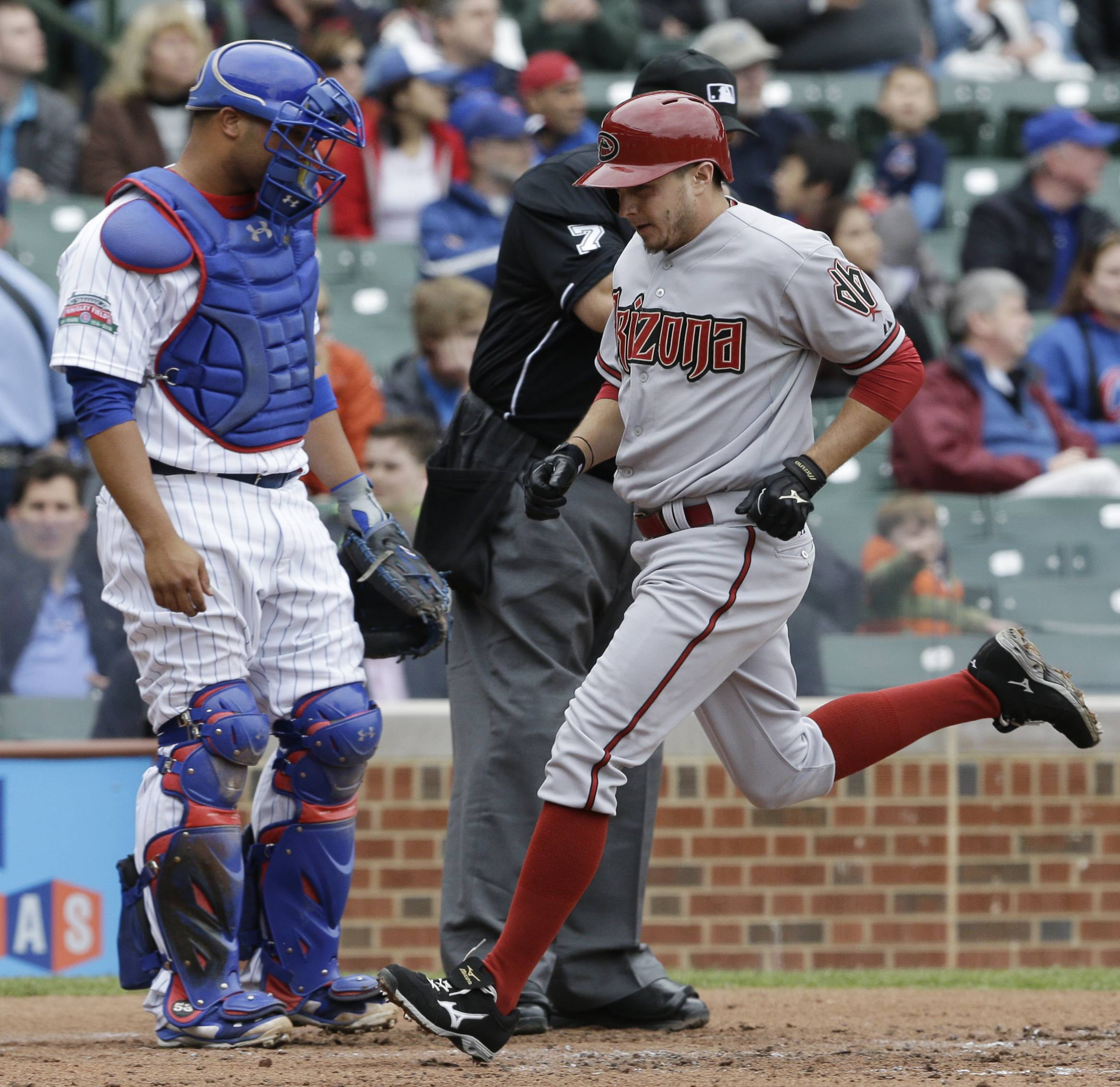Arizona Diamondbacks' Tony Campana, right, scores on a single hit by Mike Bolsinger as Chicago Cubs catcher Welington Castillo looks down during the second inning of a baseball game in Chicago, Thursday, April 24, 2014. (AP Photo/Nam Y. Huh)