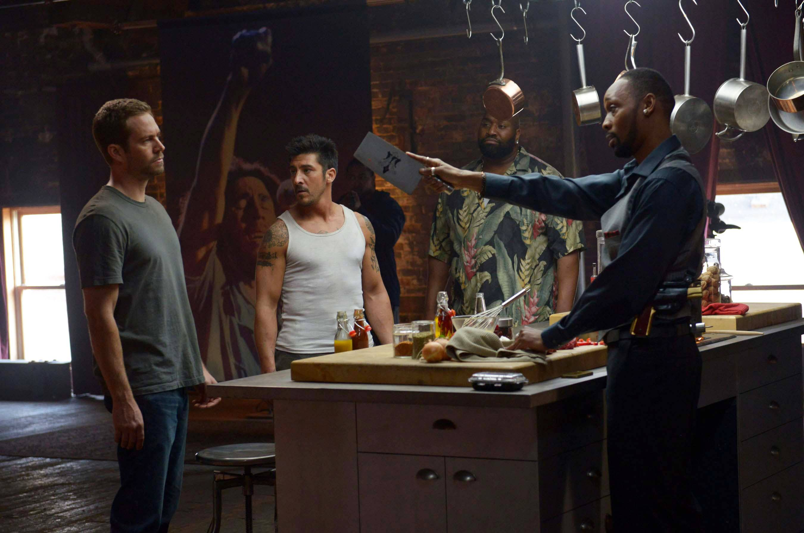 "An undercover cop (Paul Walker), left, and an ex-con (David Belle) irritate a Detroit drug kingpin (RZA) in ""Brick Mansions."""