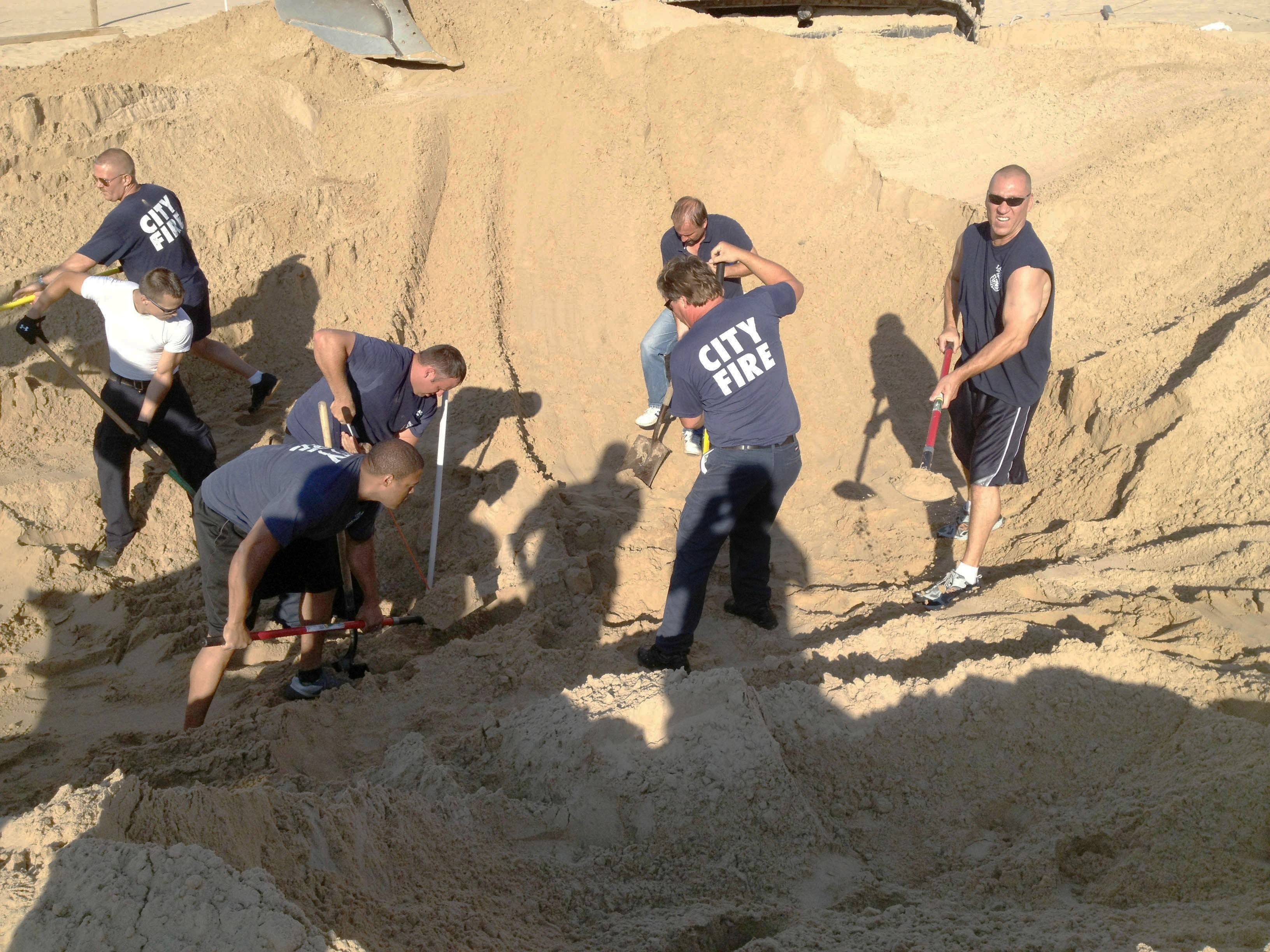 Police and firefighters dig to rescue Nathan Woessner of Sterling, Ill., who was trapped for more than three hours under about 11 feet of sand at Mount Baldy dune near Michigan City, Ind.
