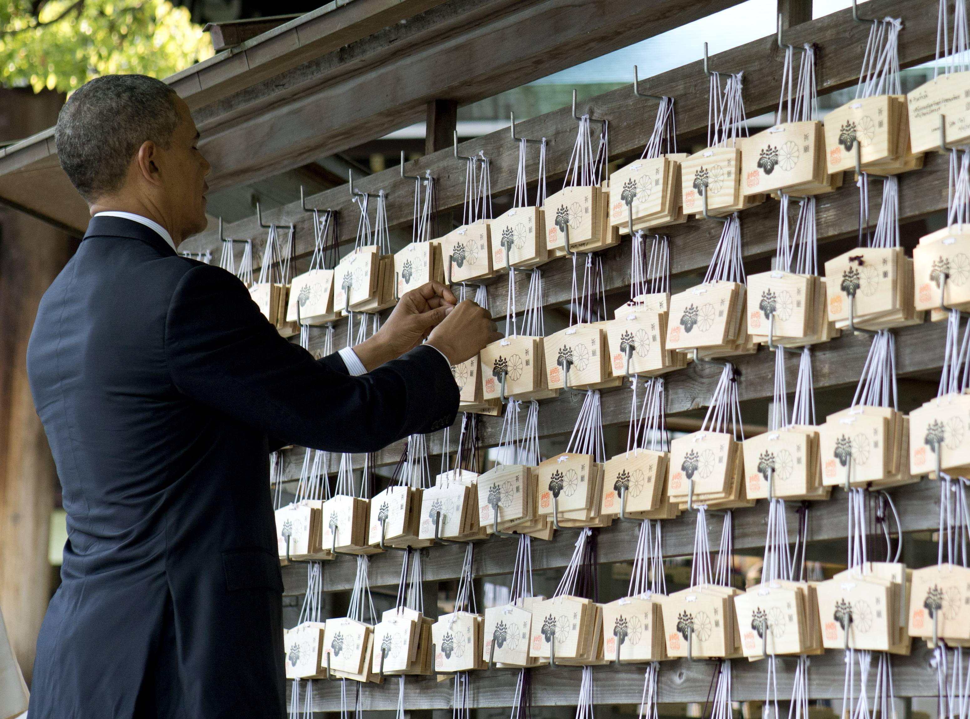 President Barack Obama places a prayer tablet on the Votive Tree as he tours Meiji Shrine in Tokyo Thursday. Showing solidarity with Japan, Obama affirmed Thursday that the U.S. would be obligated to defend Tokyo in a confrontation with Beijing over a set of disputed islands, but urged all sides to resolve the long-running dispute peacefully.