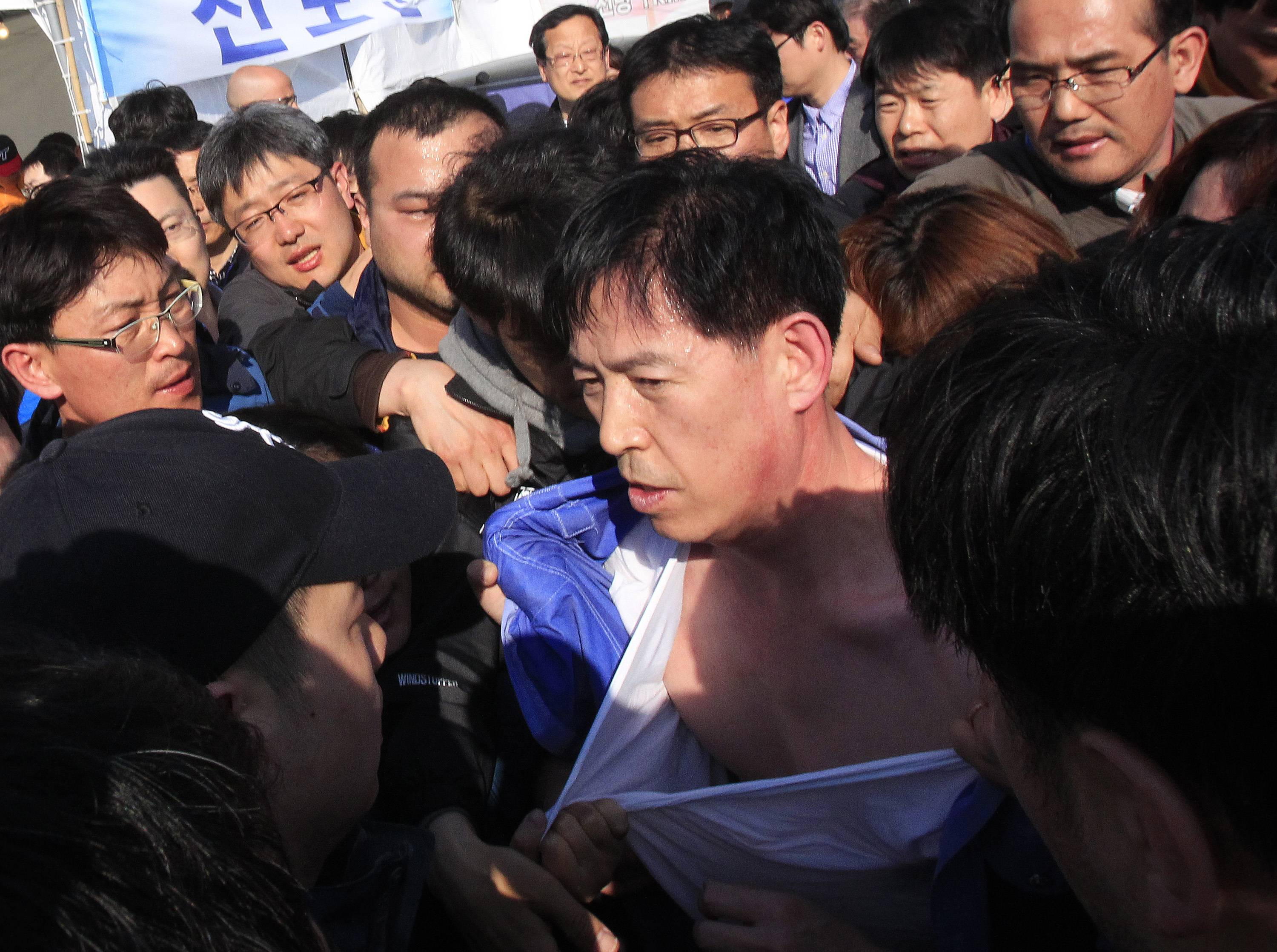 Choi Sang-hwan, South Korean Coast Guard police officer, is surround by relatives of passengers aboard the sunken ferry Sewol in the water off the southern coast as they demand for faster rescue operation, at a port in Jindo, South Korea, Thursday.