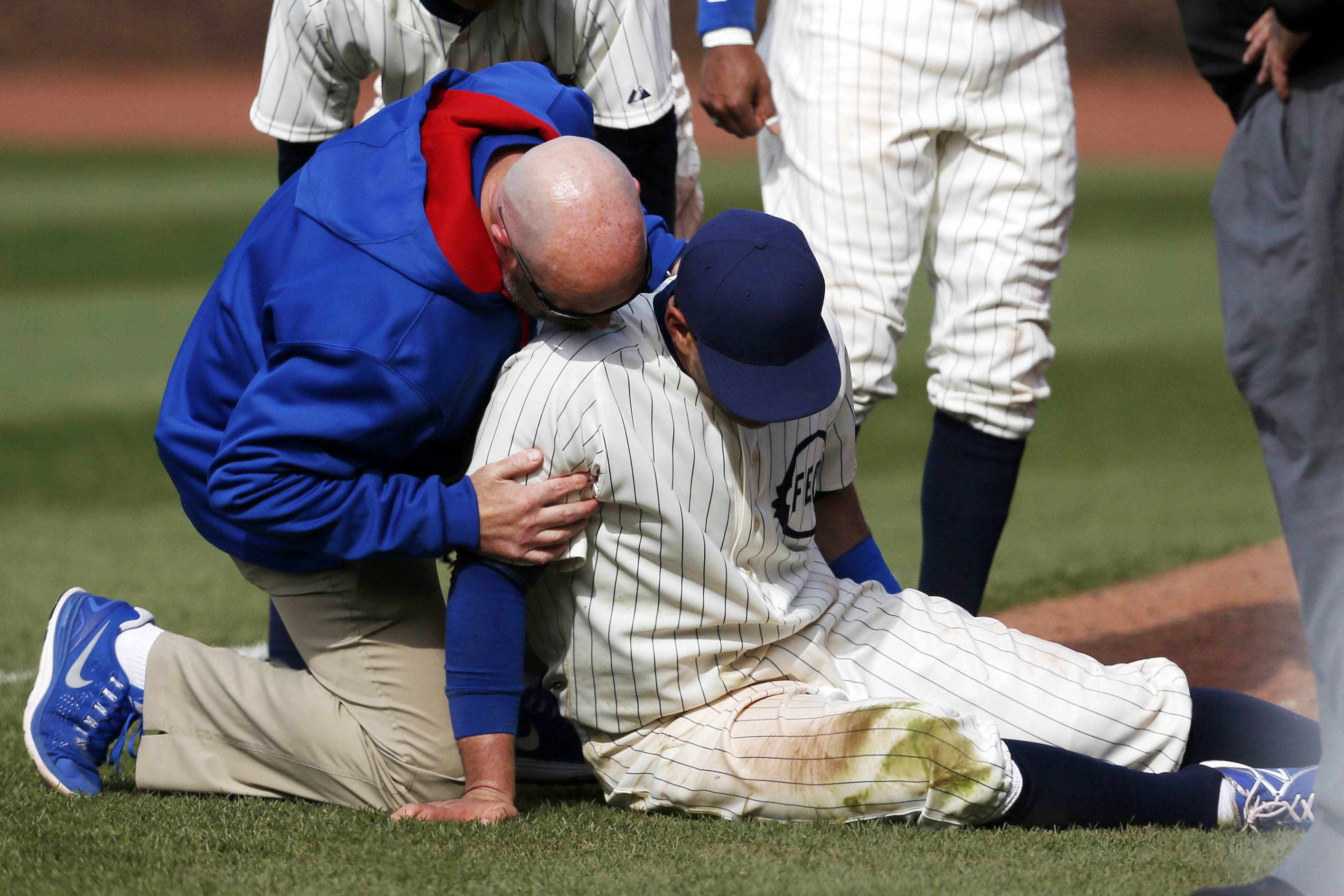 Chicago Cubs right fielder Justin Ruggiano is tended to during the ninth inning of a baseball game against the Arizona Diamondbacks at Wrigley Field in Chicago on Wednesday, April 23, 2014.