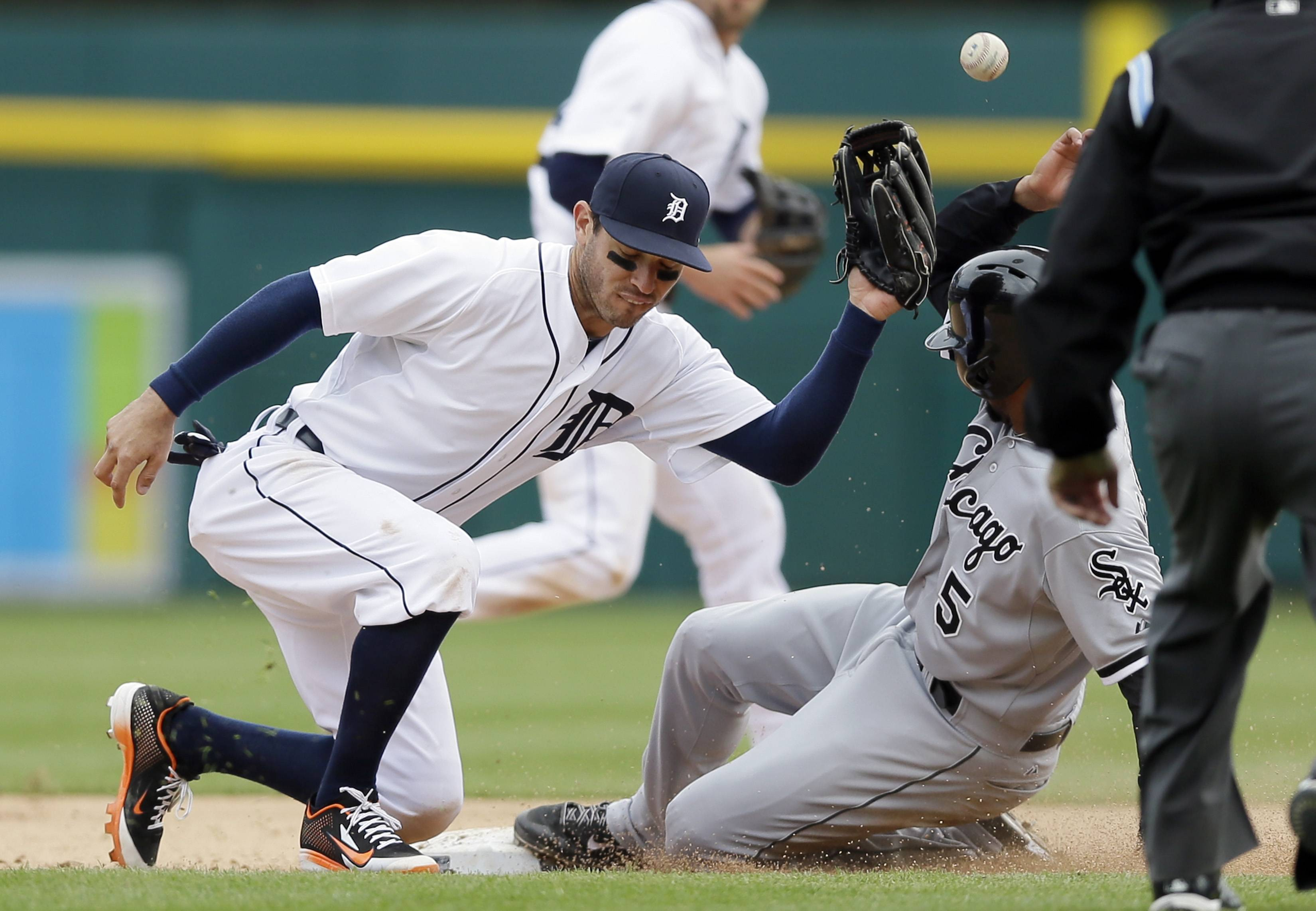 Detroit Tigers second baseman Ian Kinsler bobbles the ball as Chicago White Sox's Marcus Semien slides into second during the ninth inning of a baseball game in Detroit, Thursday, April 24, 2014. Semien was called out because of batter interference by Jose Abreu. The Tigers won 7-4.