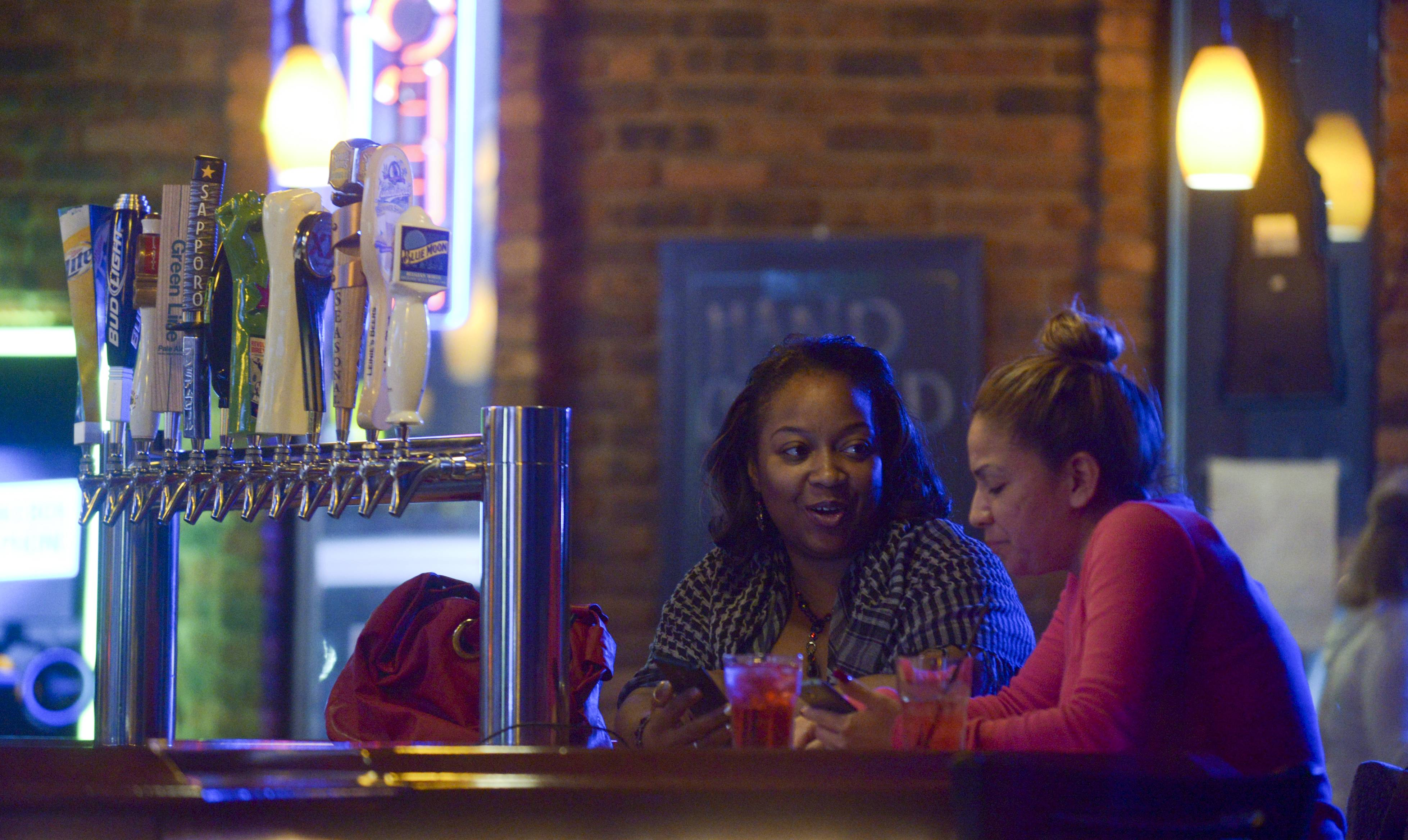 Shalyn Walker and Christina Gonzales, both of Aurora, talk over drinks at Black Door Pub in Aurora.