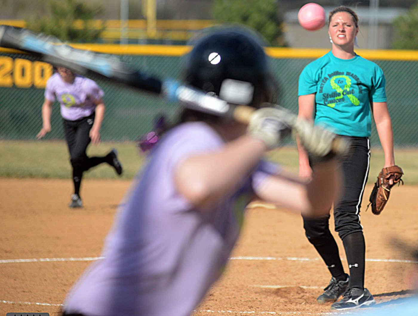 "Waubonsie Valley hurler Shannon Hohman, right, watches her offering to Metea Valley hitter Megan Arcivar during a varsity softball game at Metea Valley on Friday. Both teams worse special jerseys for the game which was themed ""Strike Out Cancer"". Various fundraising efforts, including a 50/50 raffle and bake sale, were offered to fans to raise money to fight pediatric cancer."