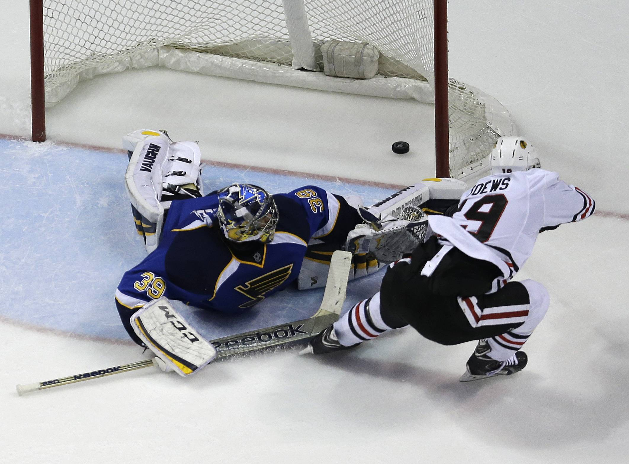 The Blackhawks' Jonathan Toews, right, scores the game-winning goal past St. Louis Blues goalie Ryan Miller during overtime in Game 5 of the first-round NHL hockey playoff series Friday in St. Louis. The Blackhawks won 3-2.