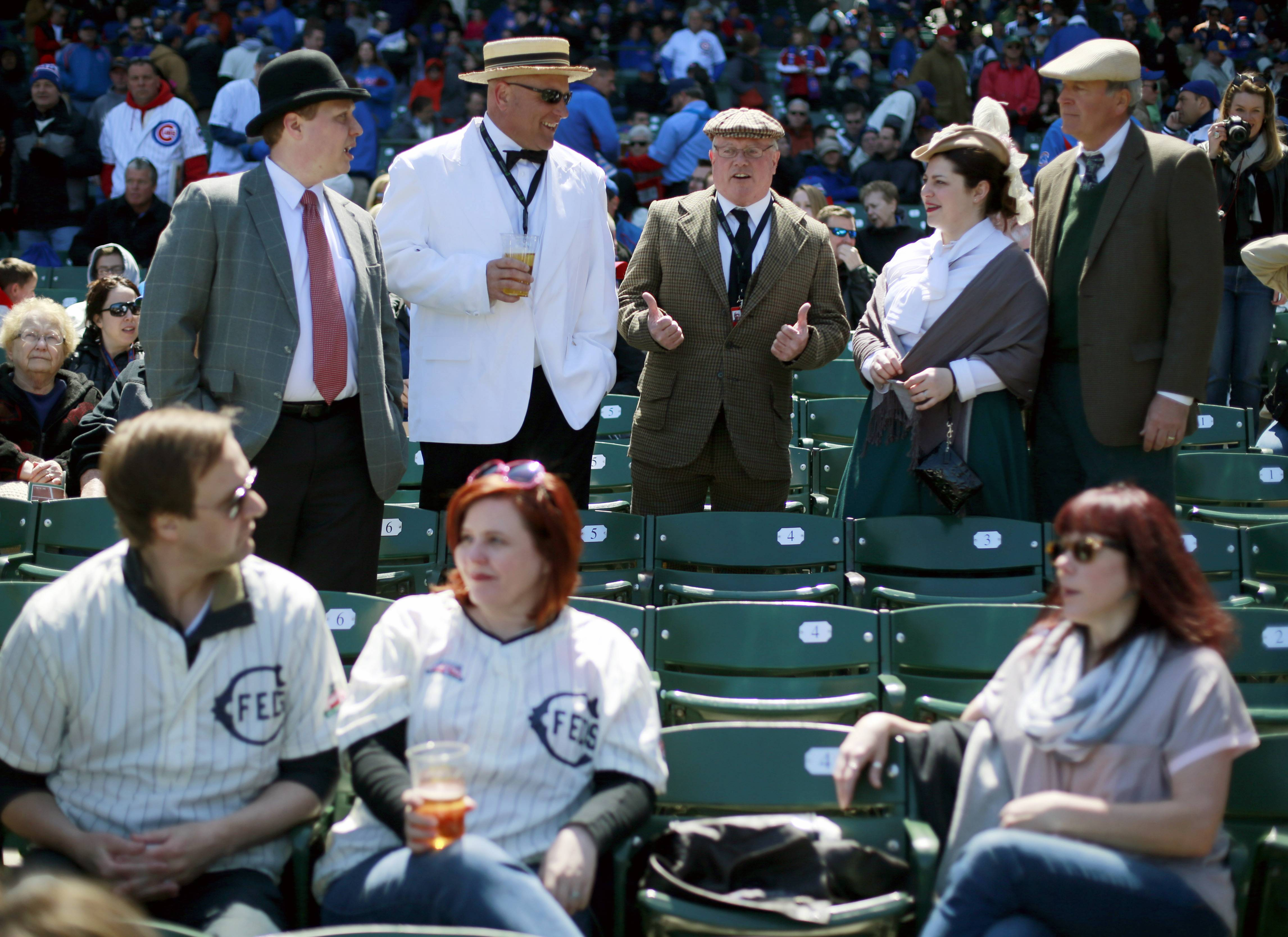 Some baseball fans dressed in period clothes, top, and others donned the replica 1914 Chicago Federals jersey on Wednesday at the 100th anniversary of the first baseball game at Wrigley Field. Several greats from Cubs and Bears history also attended the celebration.