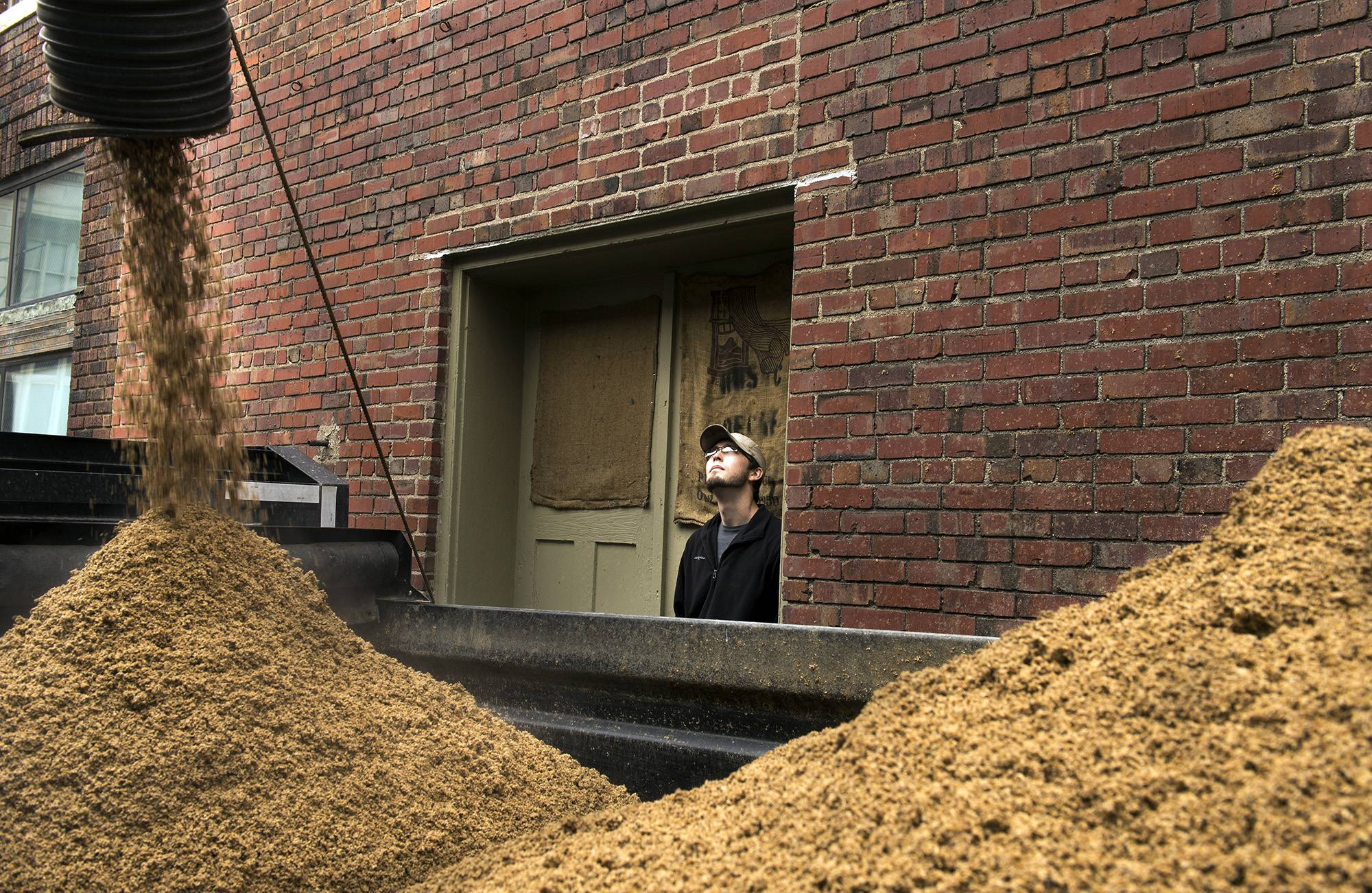Calvin West, from Meyer Dairy Farm, watches spent grain bound for the farm fill a trailer at Empyrean Brewing in Lincoln, Neb.