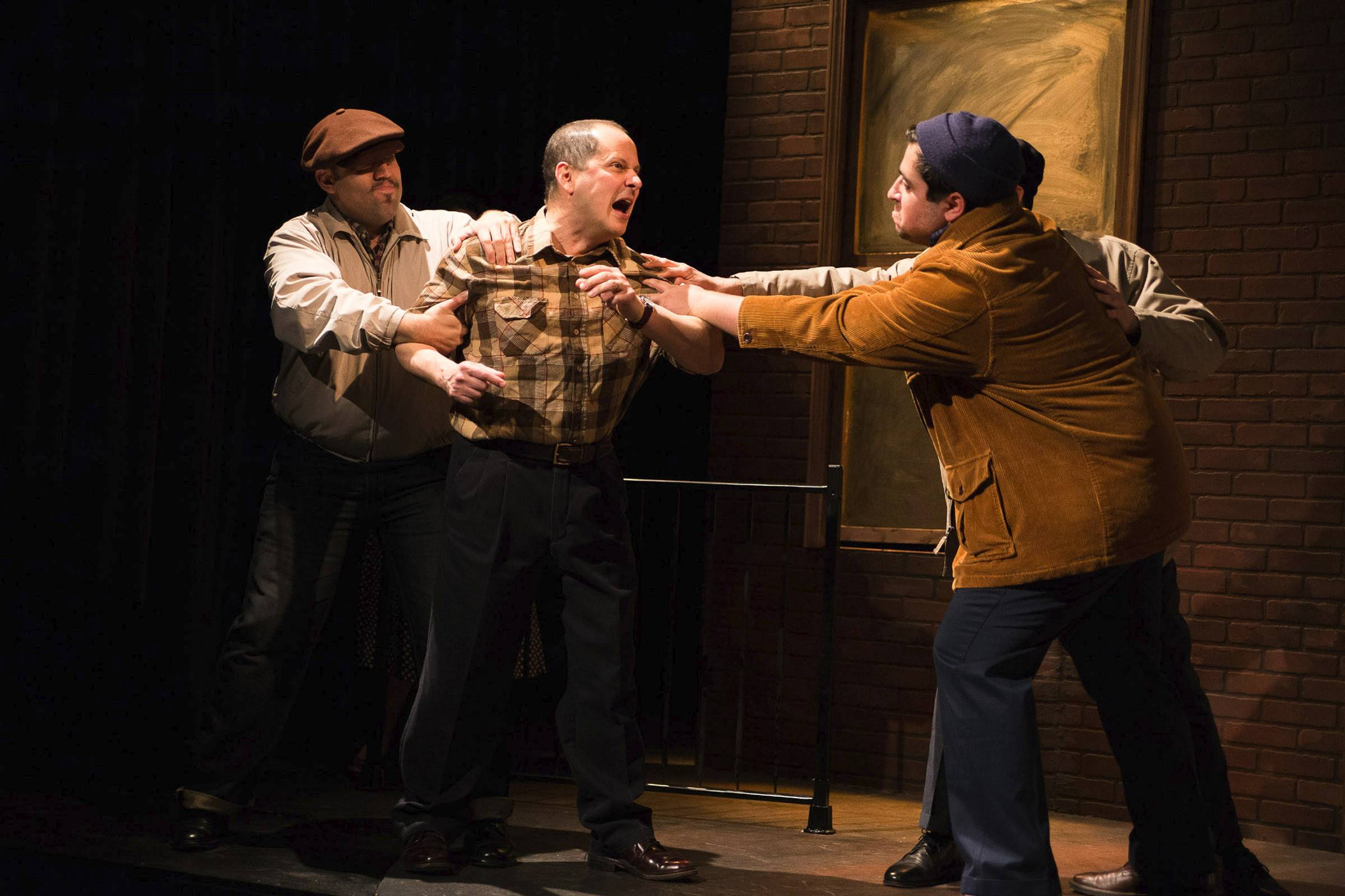 "Arthur Miller's tragic longshoreman Eddie Carbone (Ramón Camín, center) succumbs to his demons in Teatro Vista's revival of ""A View from the Bridge,"" featuring Joel Maisonet, left, of Des Plaines and Todd Garcia, right."