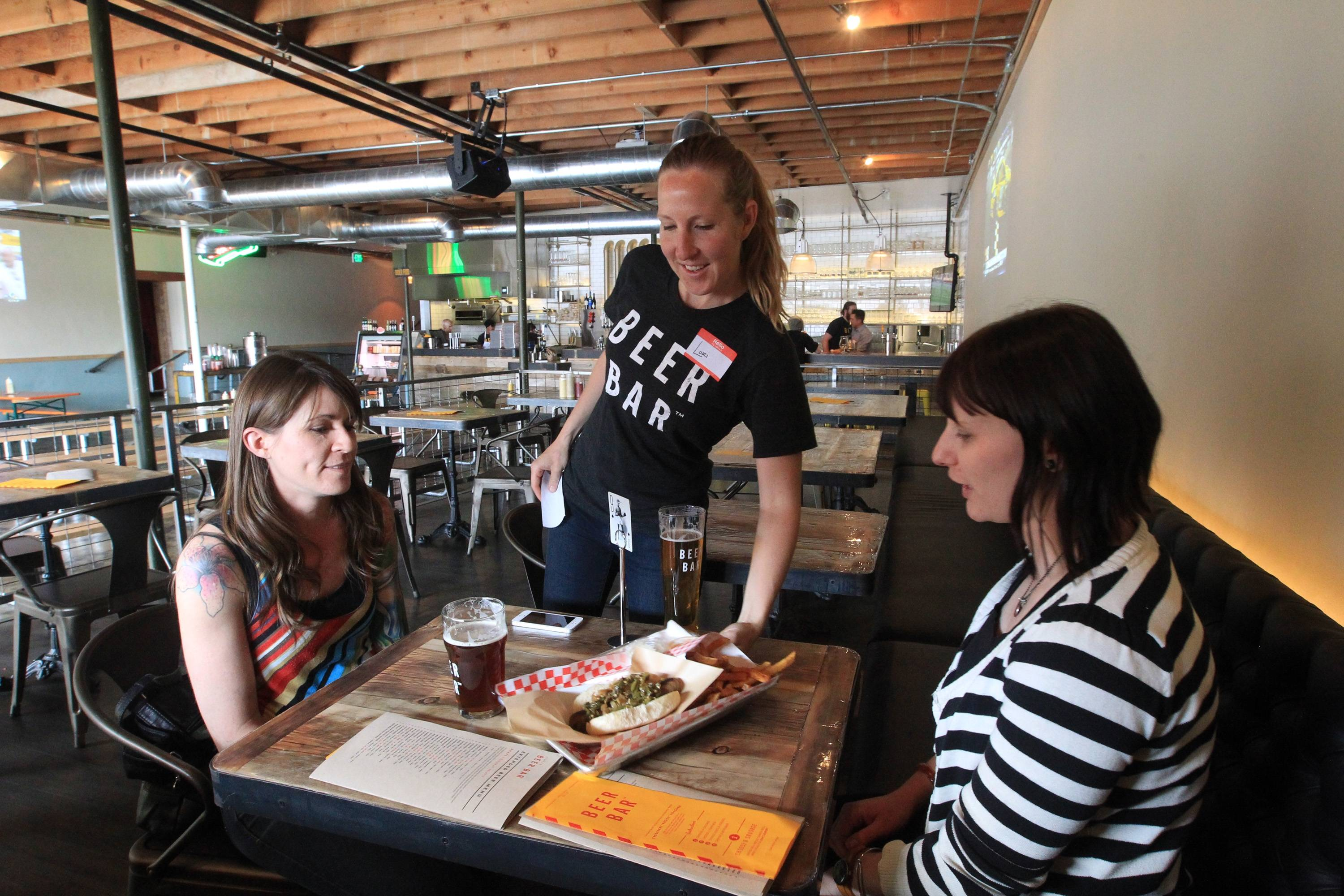 Lori Campbell, center, serves food to Andrea Latimer, right, and Nichole Peterson at Beer Bar in Salt Lake City.