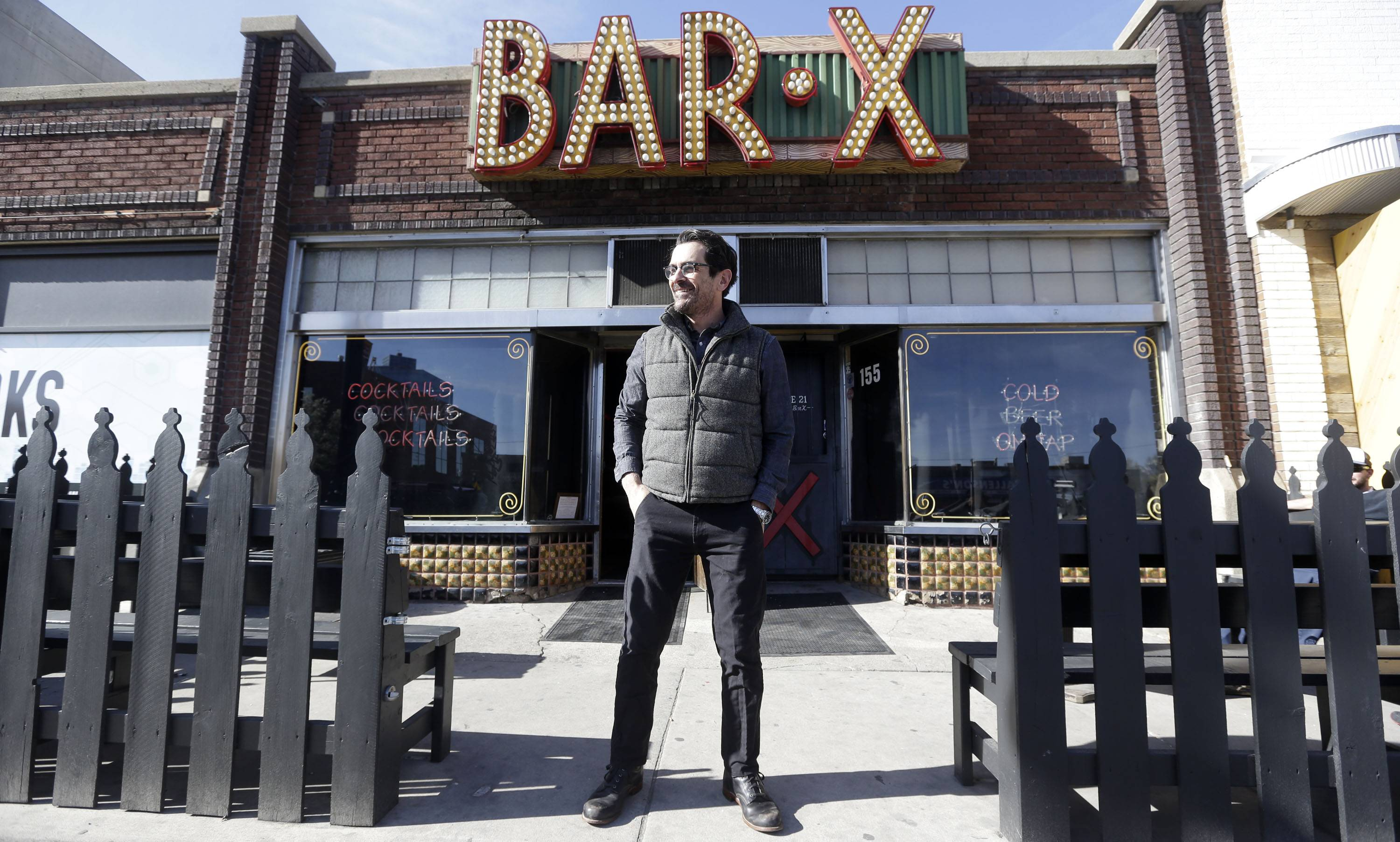 "In this April 16, 2014 photo, actor Ty Burrell, who plays bumbling dad Phil Dunphy on ABC's ""Modern Family,"" stands outside Bar X, the cocktail bar he co-owns, in Salt Lake City. Burrell just opened Beer Bar, a beer garden-like eatery next door to Bar X that serves 150 beers paired up with an array of house-made bratwursts, local breads and Belgian fries. The restaurant sports long tables and benches with high ceilings to evoke that Bavarian beer hall feel."