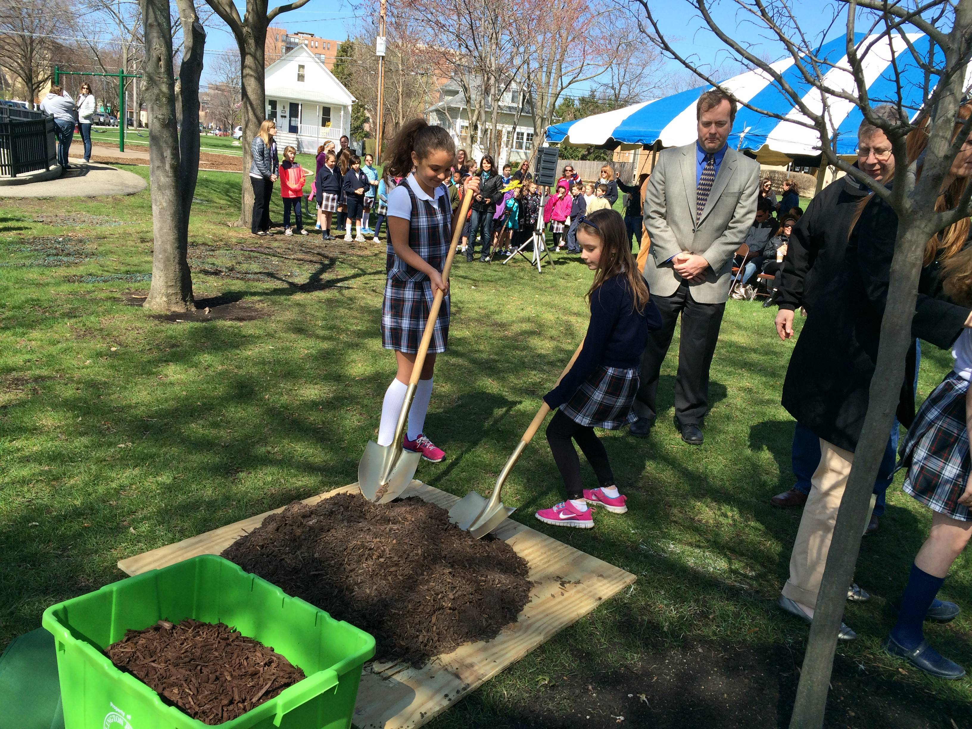 St. James Elementary students Mallory Mulligan and Isabel Klimowicz help park district Commissioner Will Ploger and Trustee Bert Rosenberg plant a new tree in Recreation Park for Arbor Day.
