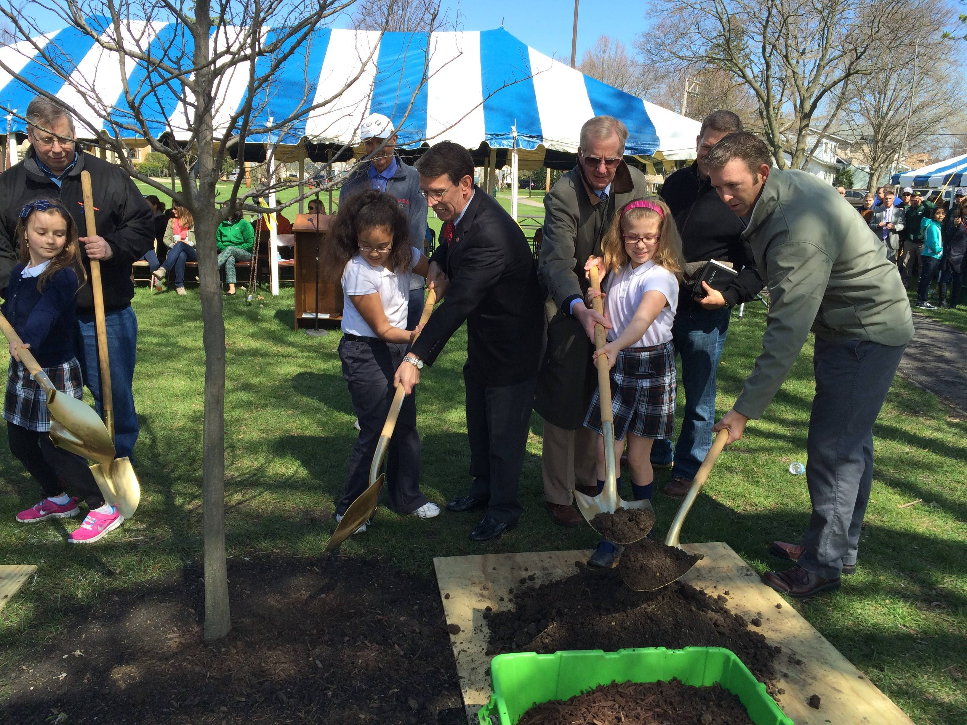 St. James Elementary students Clarise Chambers and Gabriella Wolf help Mayor Tom Hayes, Village Manager Bill Dixon and park district Commissioner Tim Gelinas plant a new tree in Recreation Park for Arbor Day in Arlington Heights on Friday.