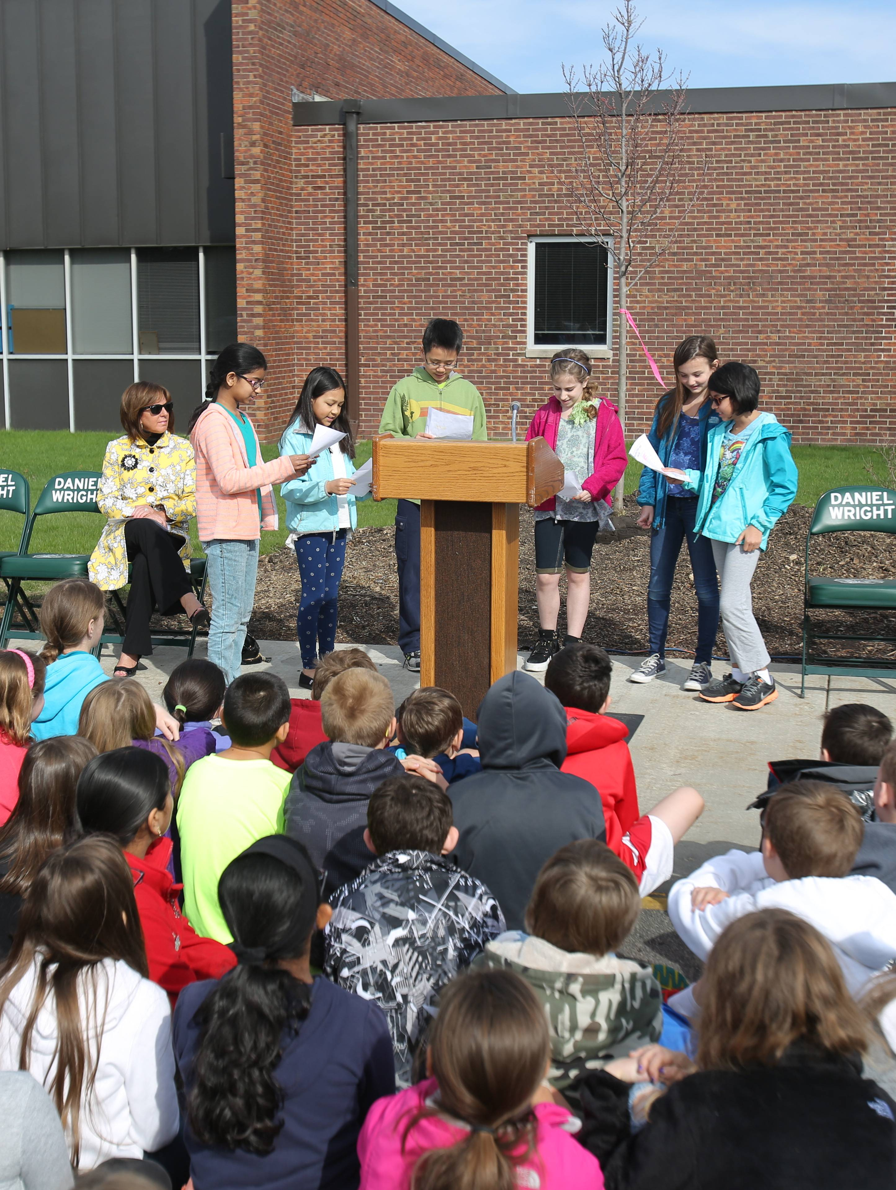 "Daniel Wright Elementary School fifth-graders take turns reading a poem called ""Trees of the Fragrant Forest"" during Friday's Arbor Day tree-planting ceremony at the Lincolnshire school."