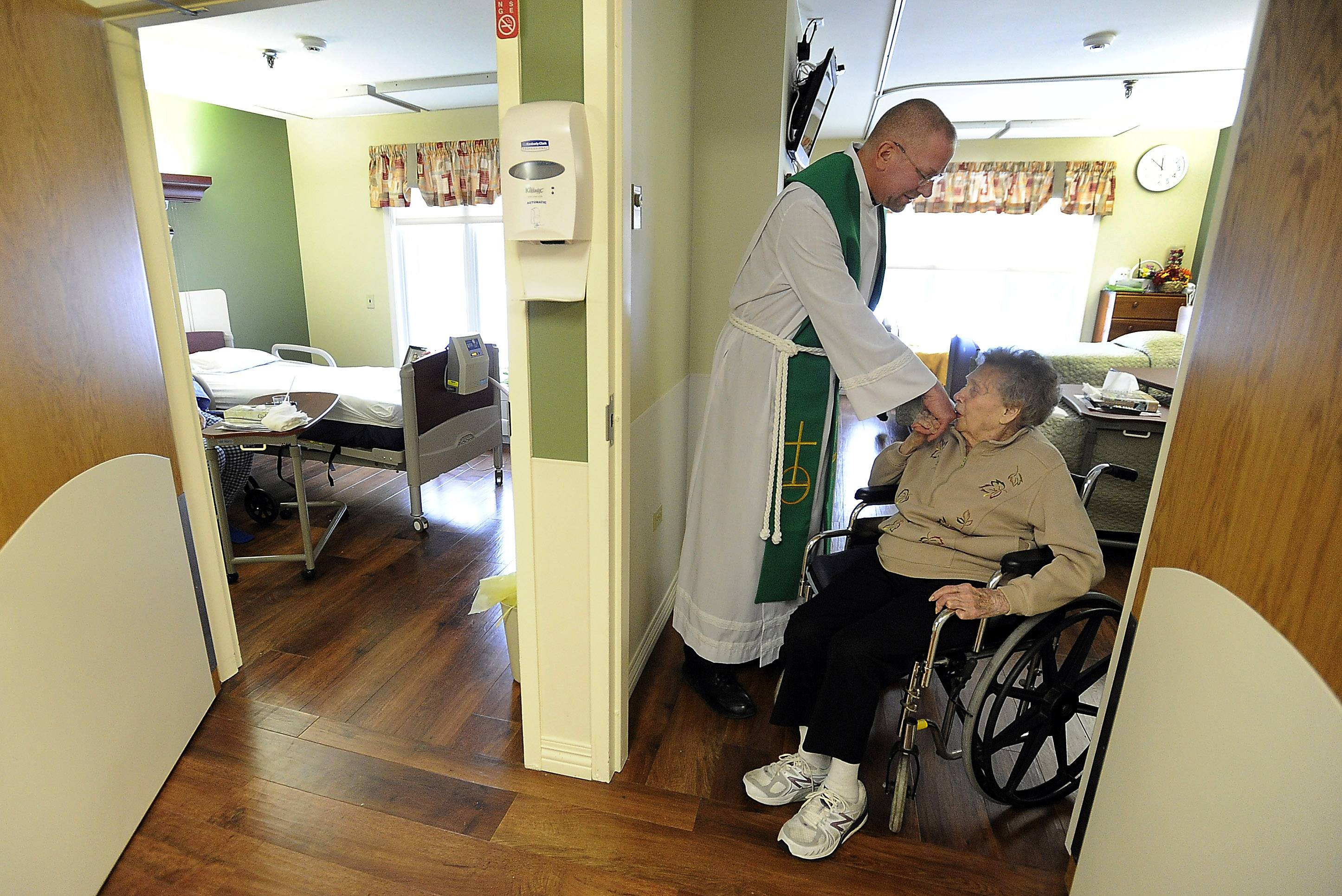 Kafader makes his daily rounds as chaplain at Friendship Village in Schaumburg getting a kiss from resident Wanda Palmieri. He makes it a point to know the first names of more than a thousand residents, greeting them with a smile and a prayer.