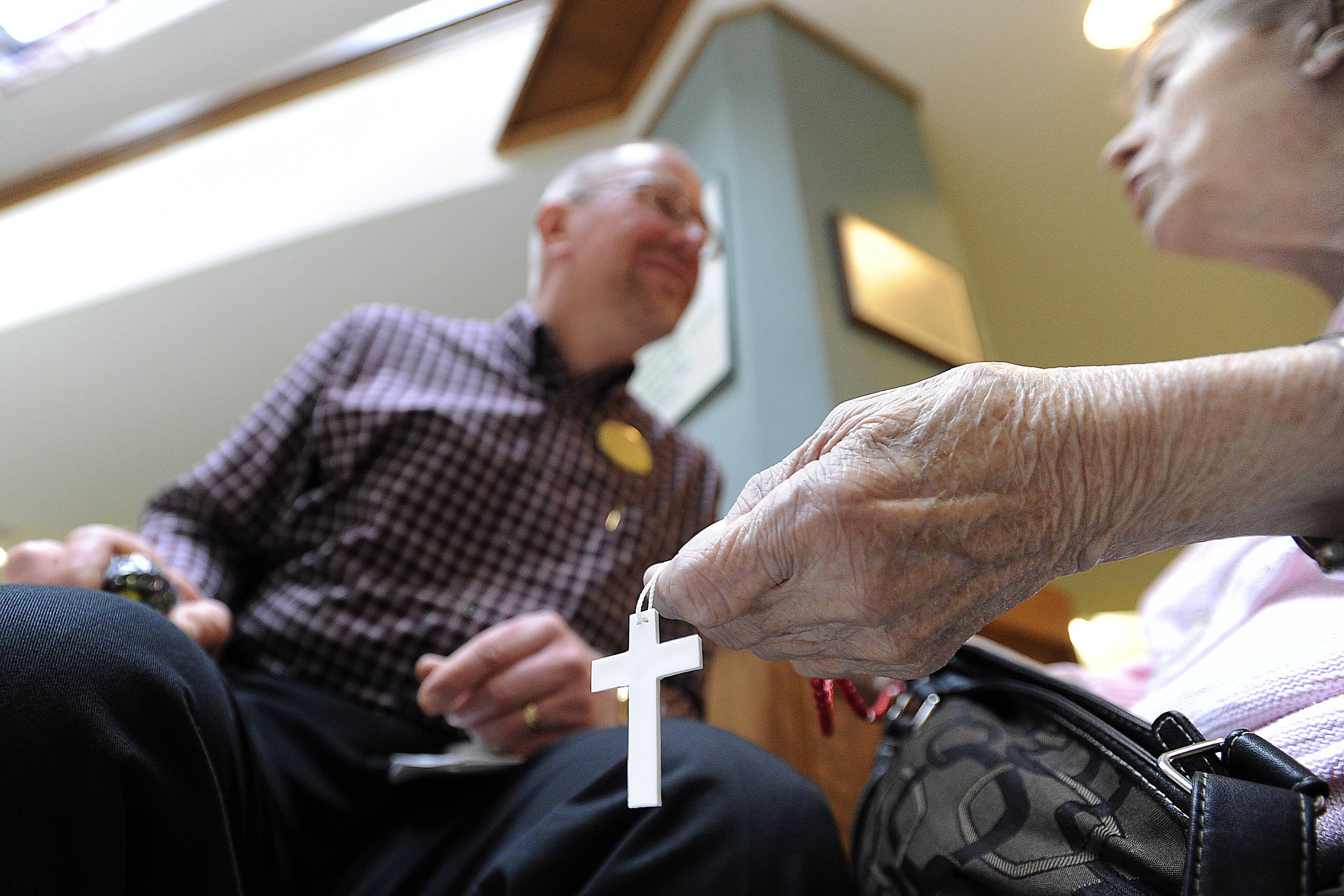 The Rev. Shawn Kafader visits with Rosie Picciarello, a resident of Friendship Village on his daily rounds. The chaplain makes rosaries at home and gives them to the residents.