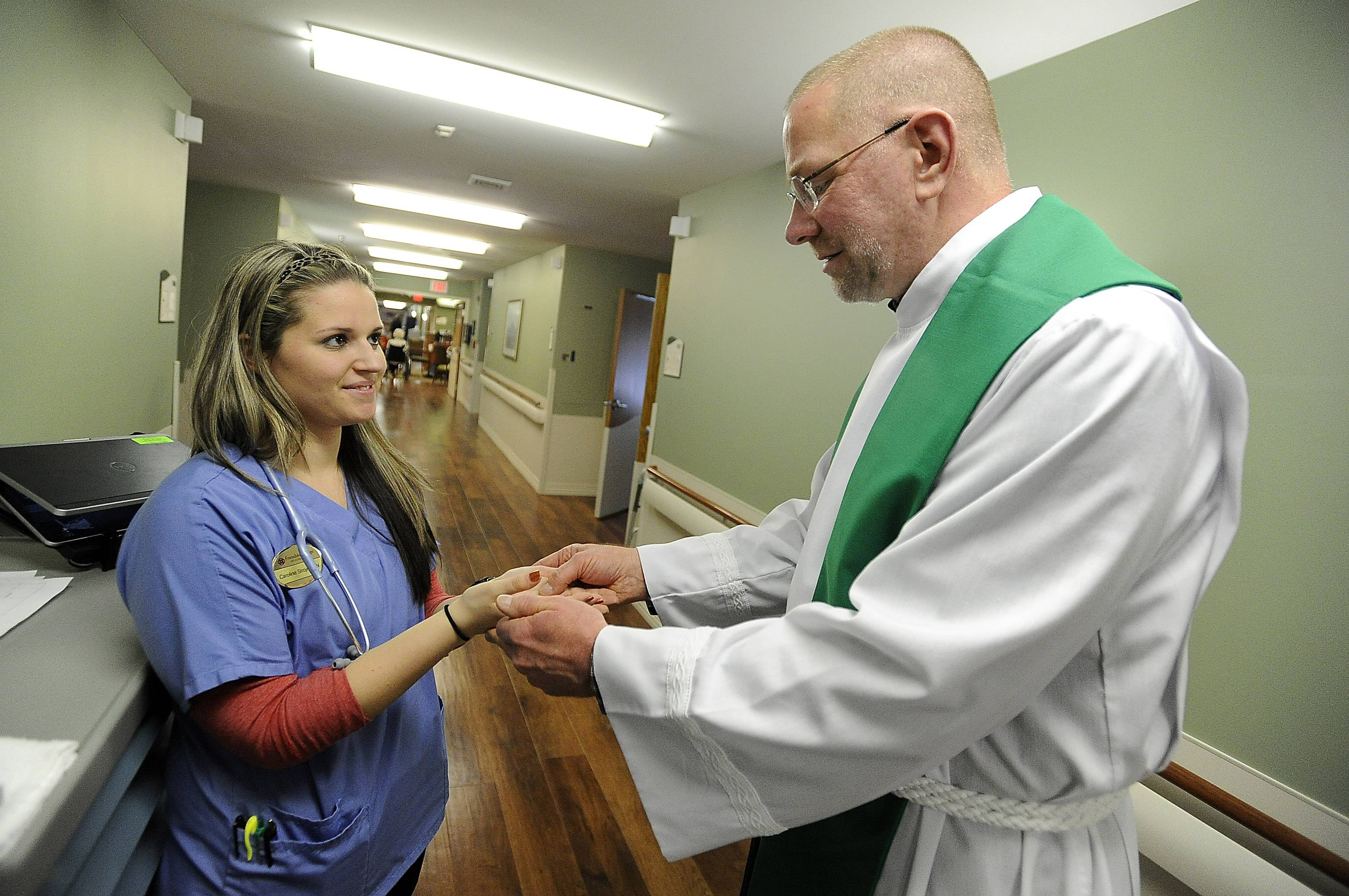 Using sacred anointing oil on the hands of staff nurse Caroline Strojny of Schaumburg, Kafader reprises the presence of God in her life. He says this blessing allows staff members to do good work.