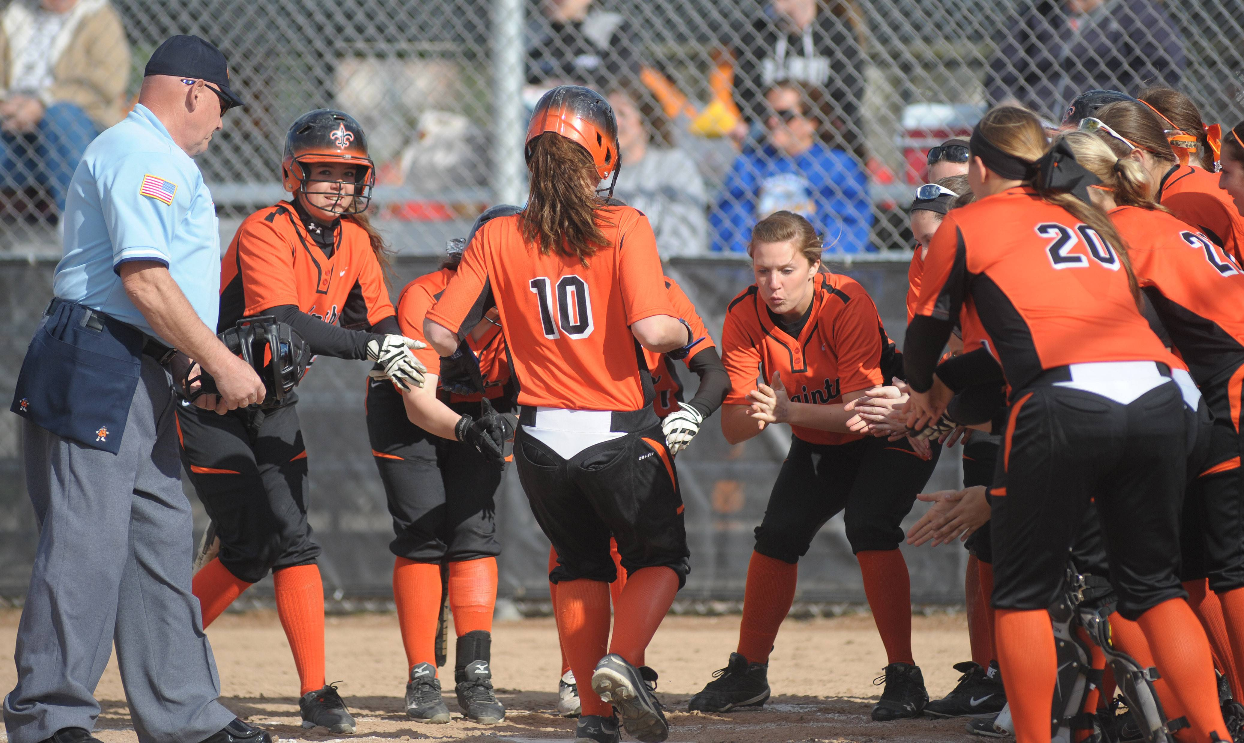 St. Charles East's Kate Peterburs is greeted by her teammates at home plate after her home run Friday against Lyons.