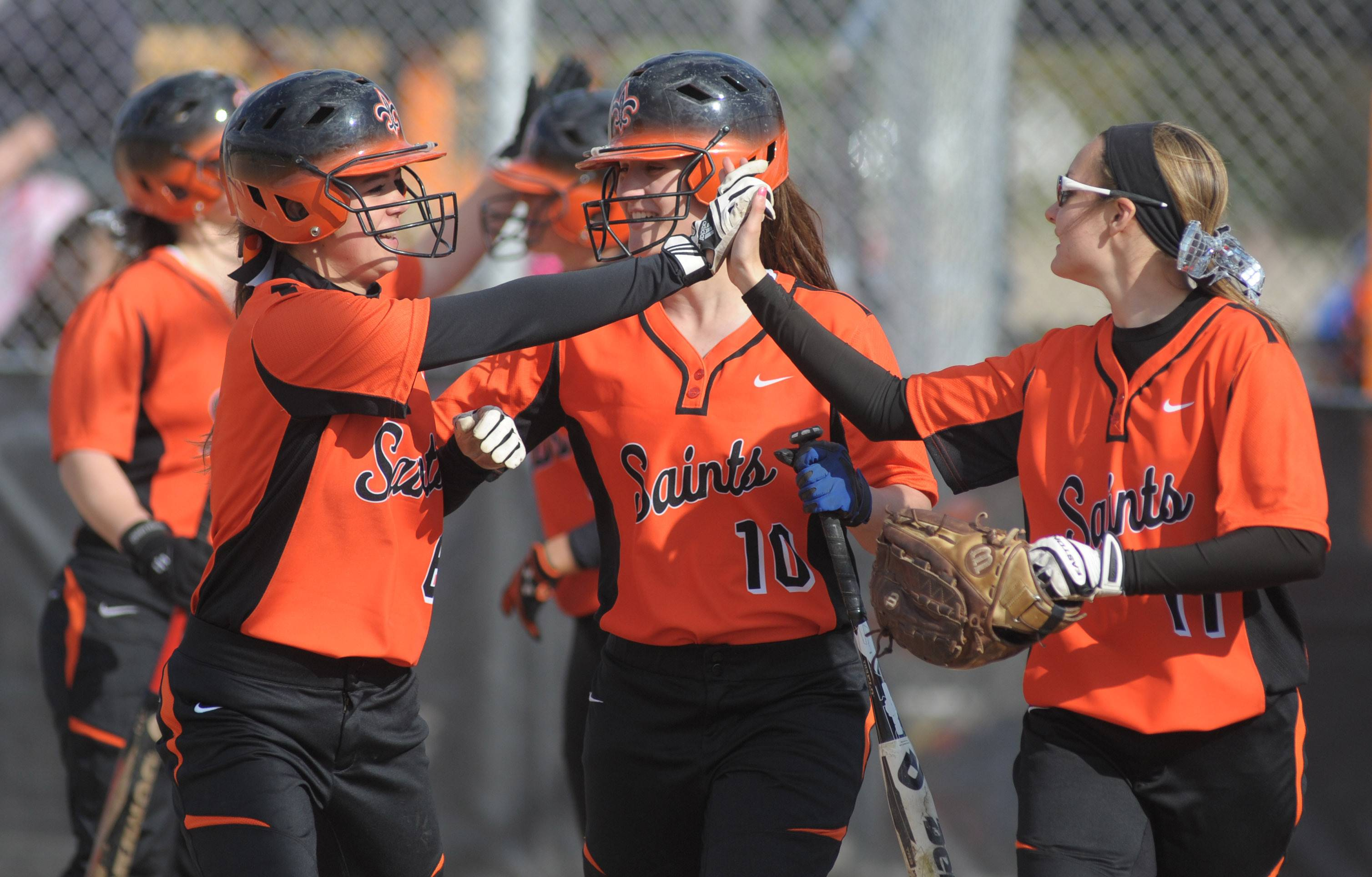 St. Charles East's Olivia Cheatham, left, Kate Peterburs, center, and Tess Hupe celebrate after Peterburs' home run in the first inning vs. Lyons on Friday, April 25.