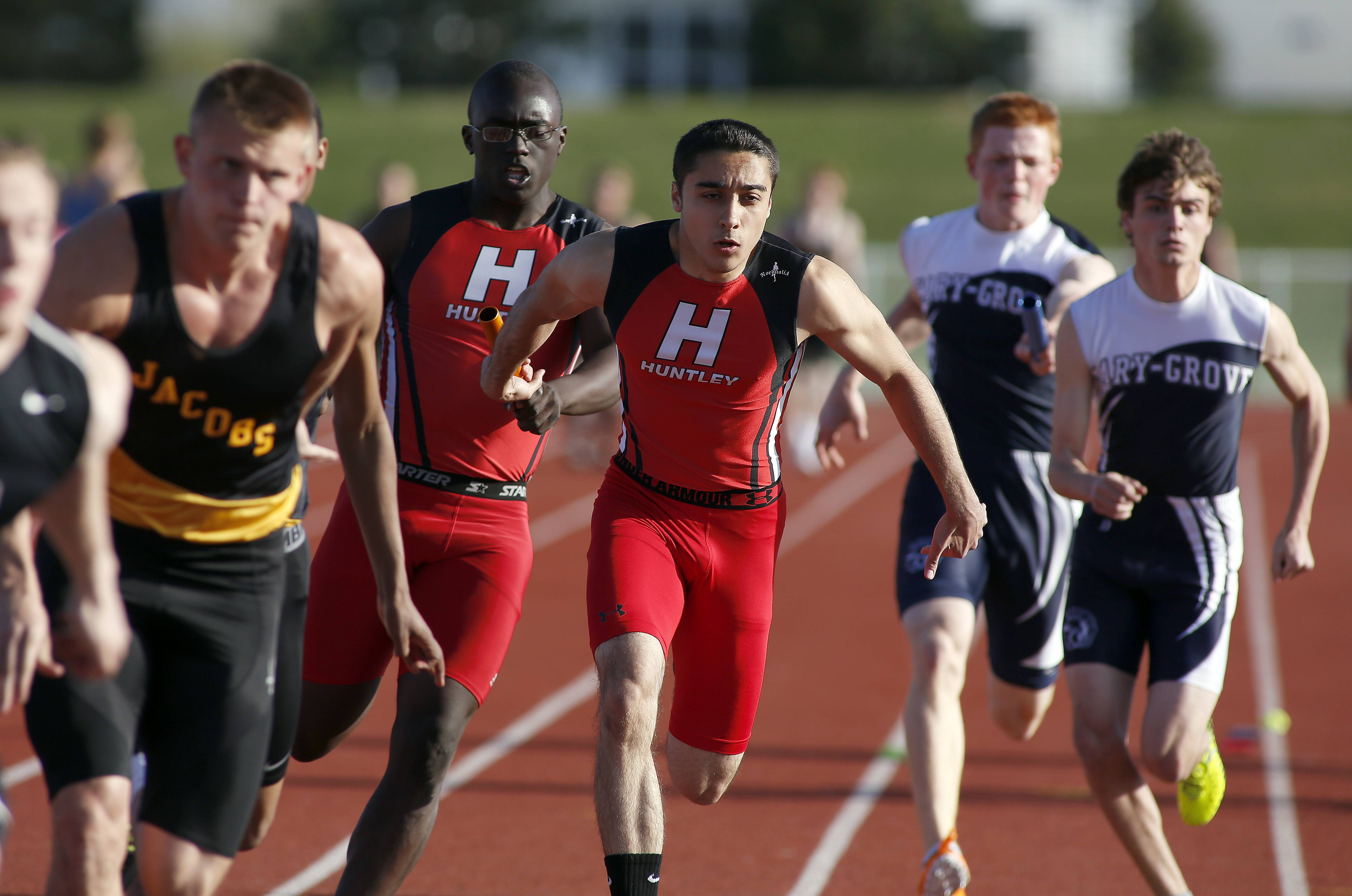 Huntley's Tim McCloyn, left and Aasem Awwad hand off the baton in the 4x100 relay during the McHenry County Track and Field Championships Friday in Huntley.