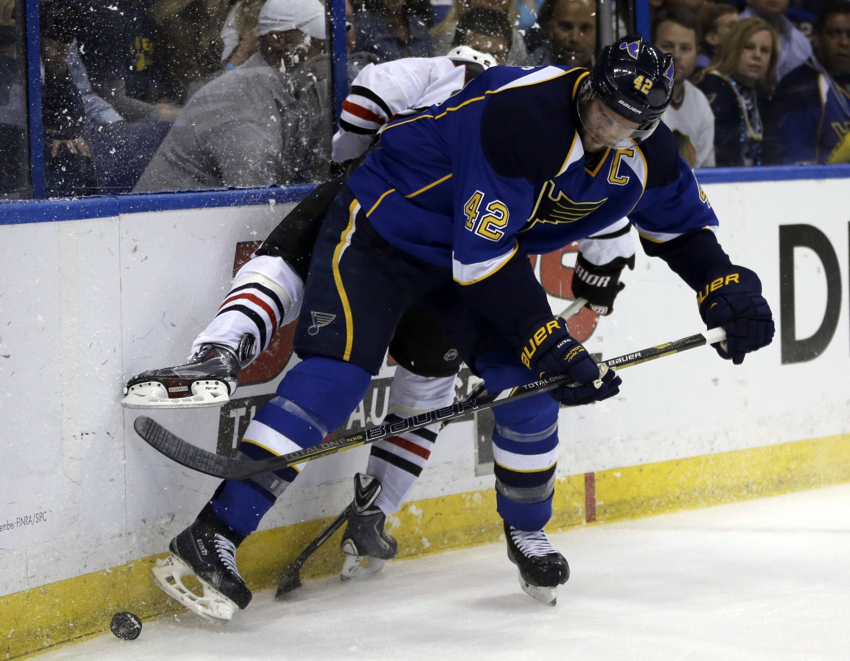 St. Louis Blues' David Backes, front, checks Chicago Blackhawks' Marcus Kruger, of Sweden, into the boards while chasing after a loose puck during the third period.