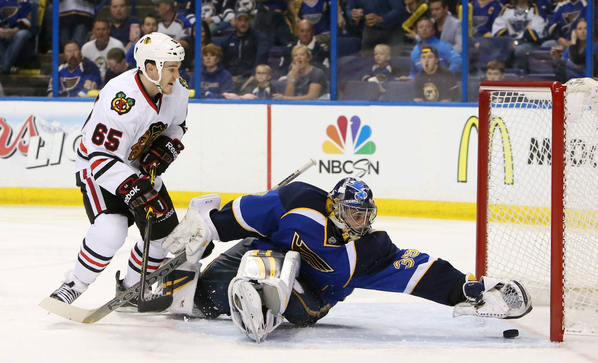 St. Louis Blues goaltender Ryan Miller reaches back just in time to prevent a goal as Chicago Blackhawks center Andrew Shaw pressures in second period action.