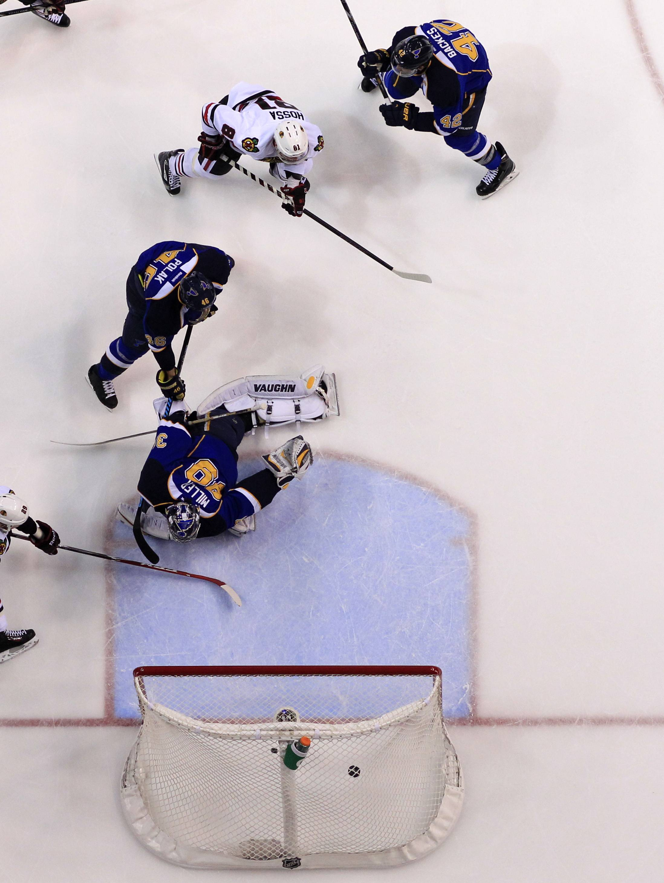 Chicago Blackhawks' Marian Hossa, top left, of Slovakia, scores past St. Louis Blues goalie Ryan Miller, bottom, Roman Polak, of the Czech Republic, and David Backes, top right, during the first period.