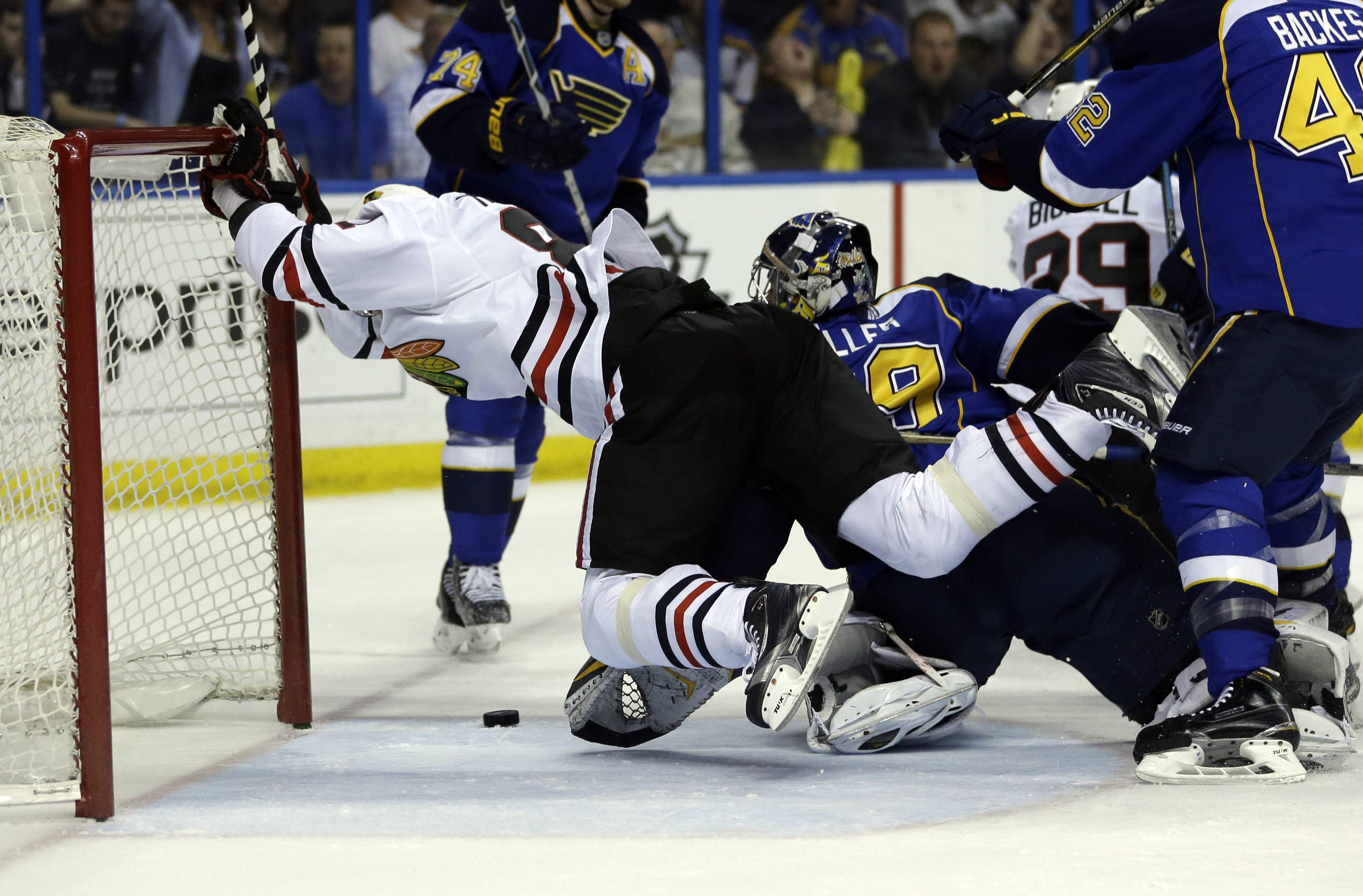 Chicago Blackhawks' Marian Hossa, of Slovakia, scores past St. Louis Blues goalie Ryan Miller, right, during the first period in Game 5.