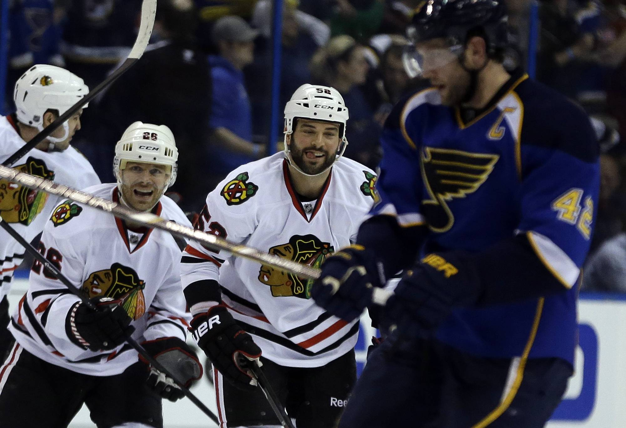 Chicago Blackhawks' Michal Handzus, of Slovakia, and teammate Brandon Bollig, center, celebrate as St. Louis Blues' David Backes, right, skates off the ice at the end of Game 5.