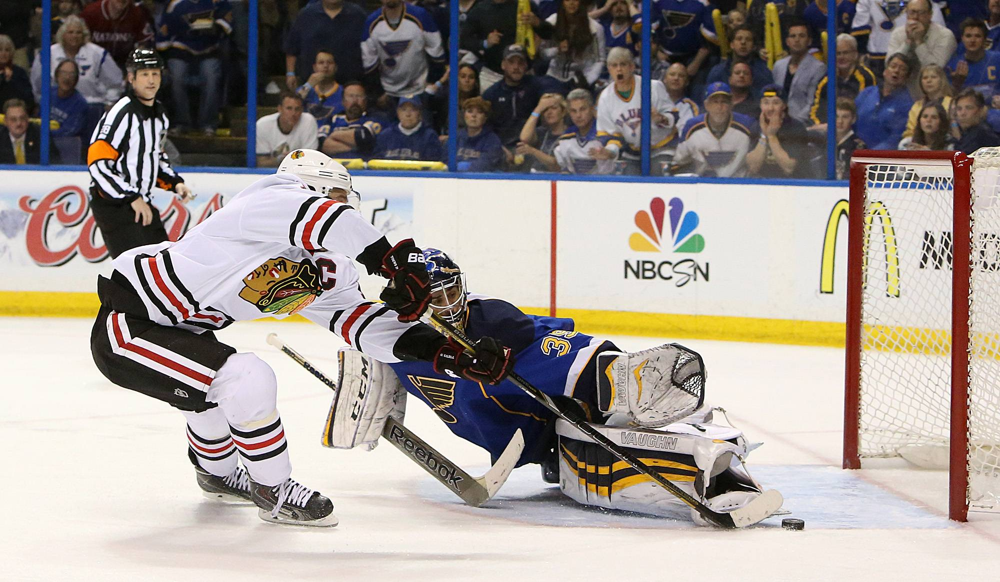 Chicago Blackhawks center Jonathan Toews (left) scores the game-winning goal in overtime past St. Louis Blues goaltender Ryan Miller.
