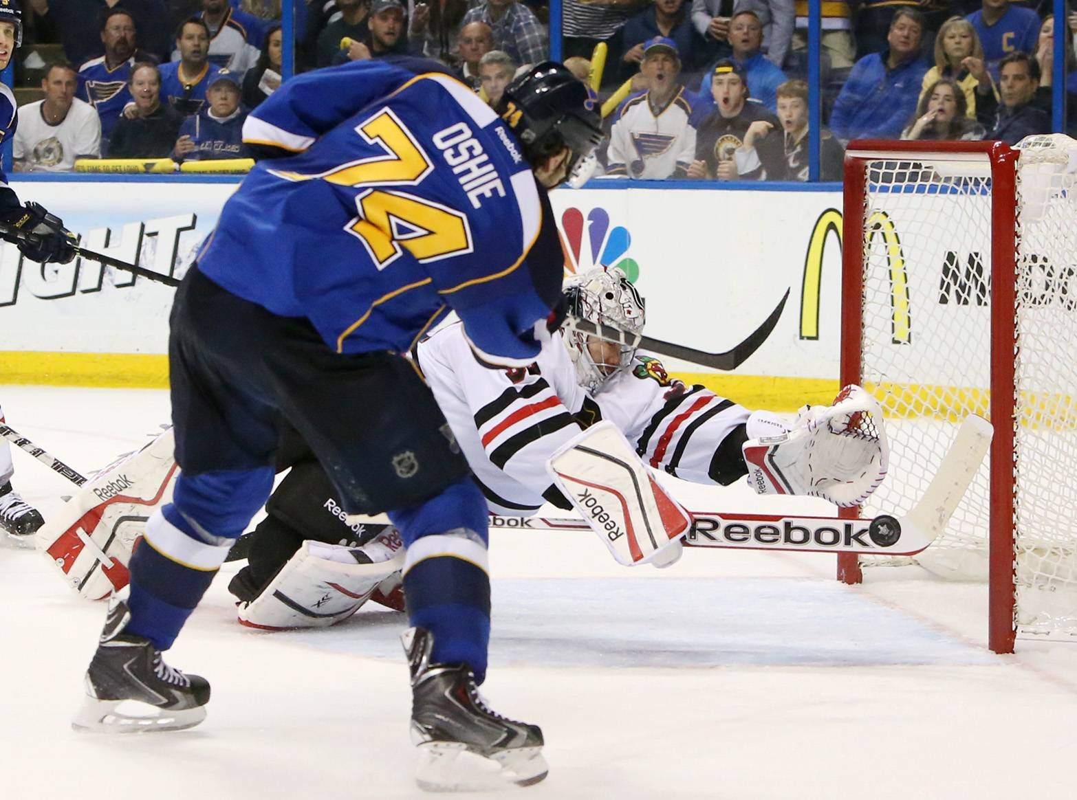 Chicago Blackhawks goaltender Corey Crawford dives back across the crease to try and stop a wide-open shot by St. Louis Blues right wing T.J. Oshie in third period action.