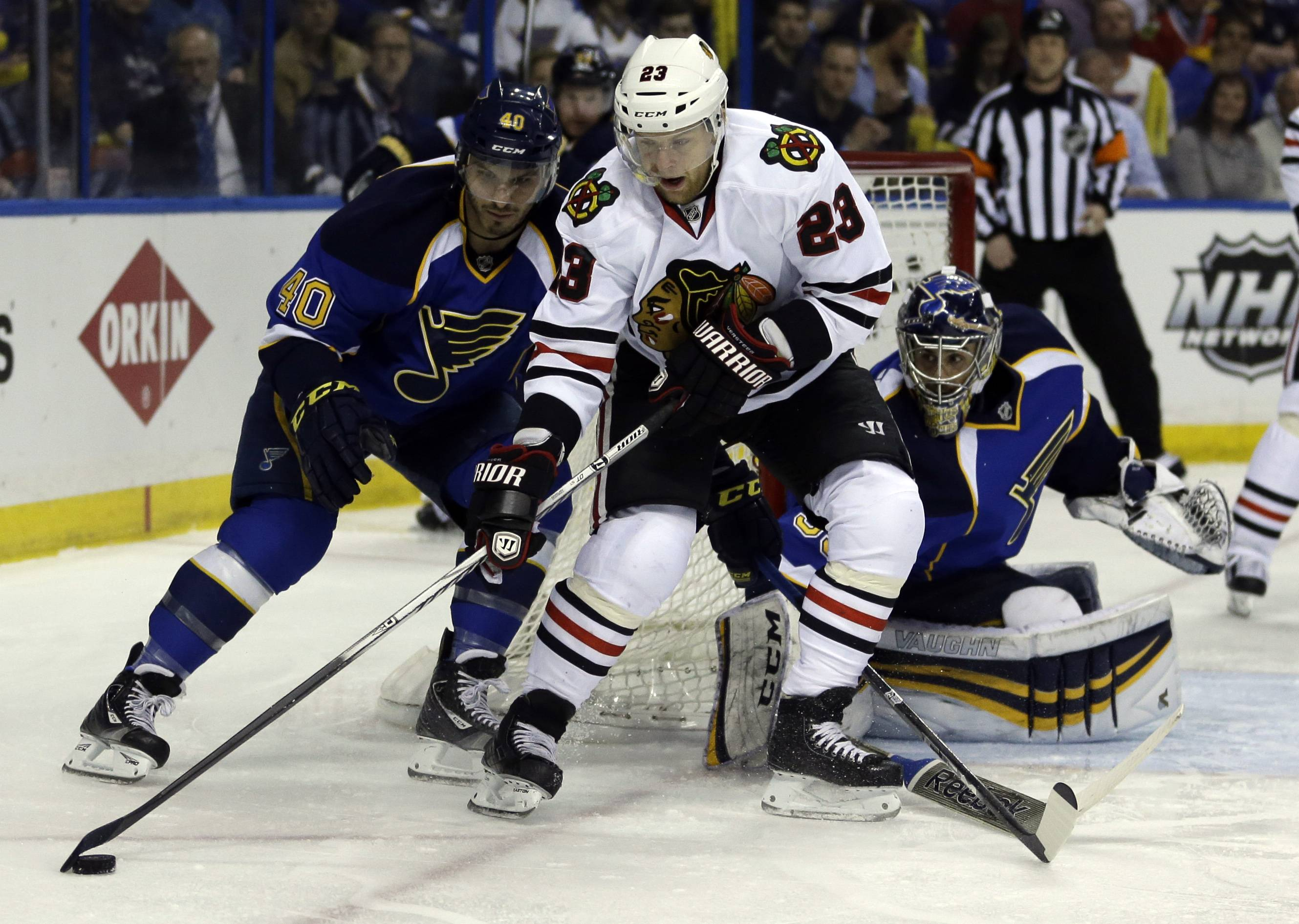 Chicago Blackhawks' Kris Versteeg,center, handles the puck as St. Louis Blues goalie Ryan Miller, right, and Maxim Lapierre, left, defend during the first period.
