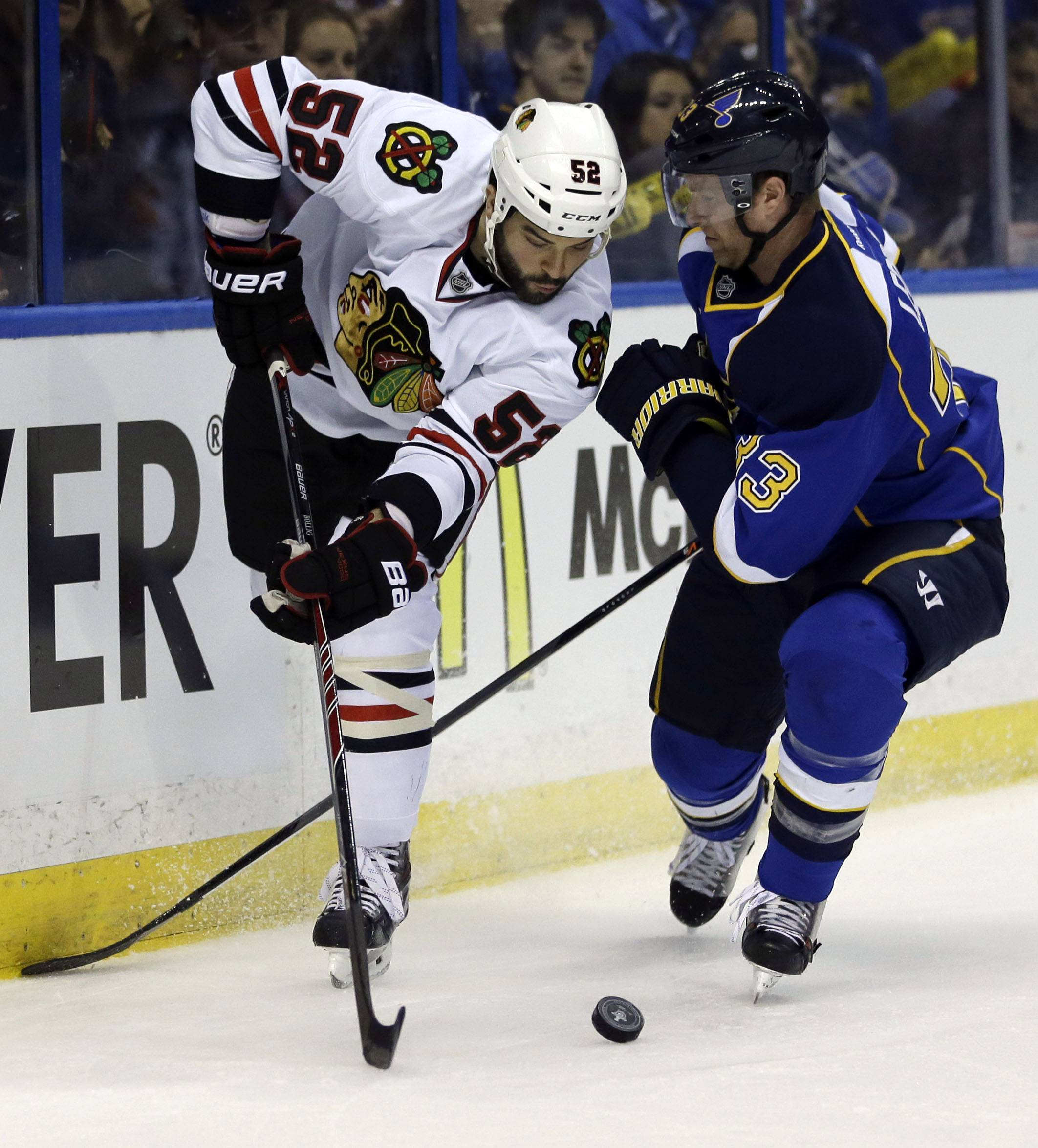 Chicago Blackhawks' Brandon Bollig, left, passes the puck as St. Louis Blues' Jordan Leopold defends during the first period .