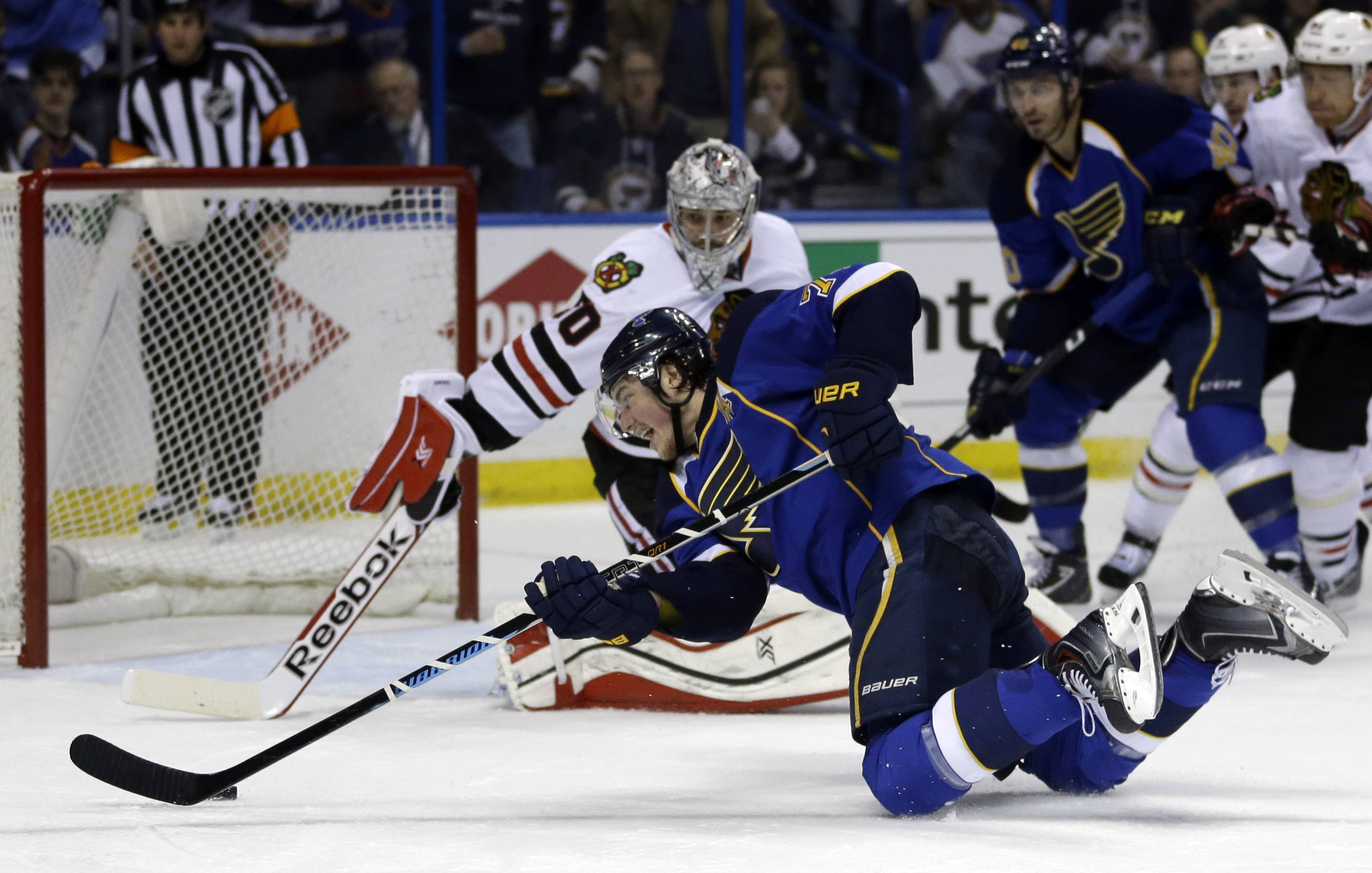 St. Louis Blues' T.J. Oshie, front, reaches for a puck to score past Chicago Blackhawks goalie Corey Crawford during the second period.