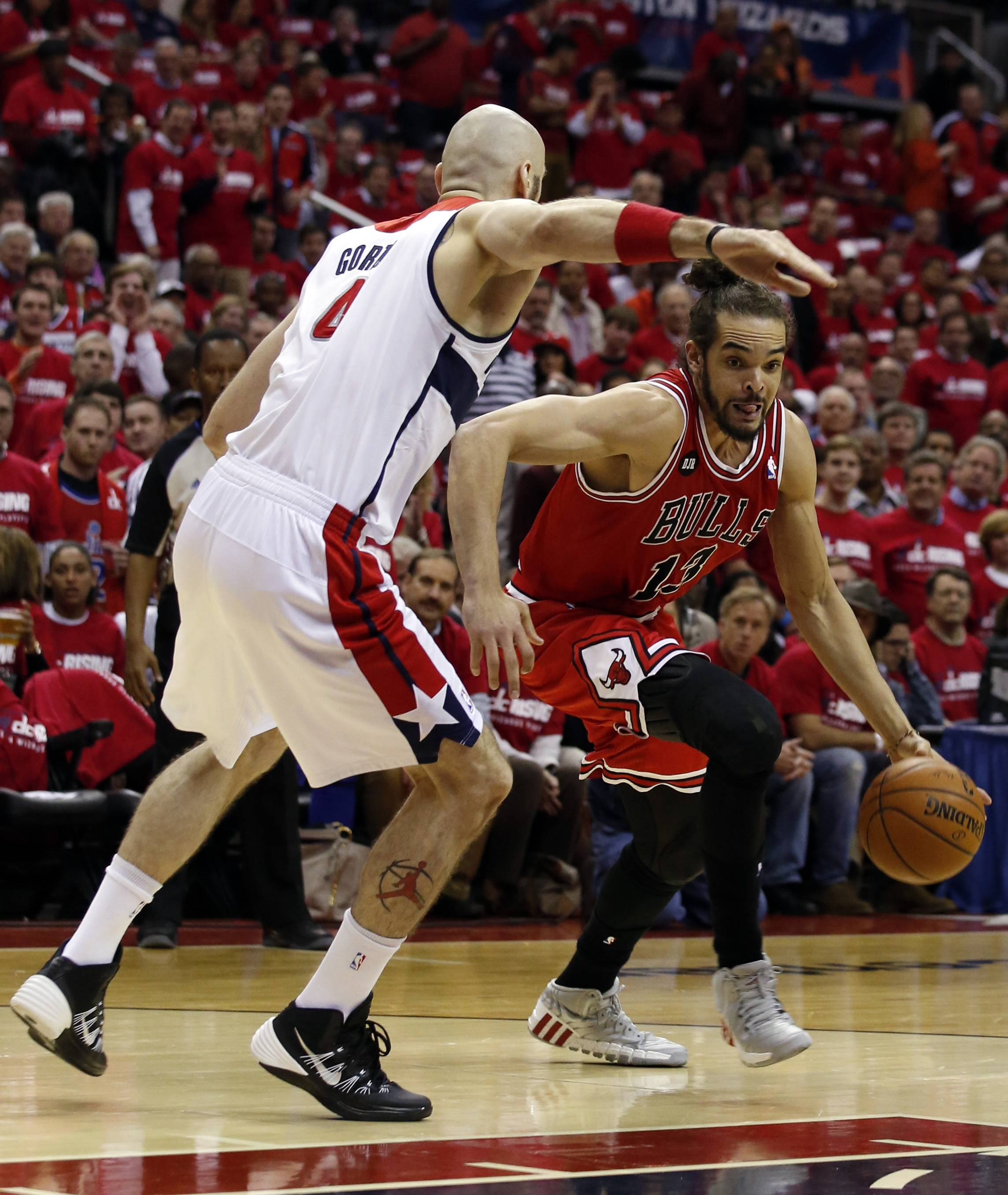 Chicago Bulls center Joakim Noah (13) drives past Washington Wizards center Marcin Gortat (4), from Poland, in the first half of Game 3 of an opening-round NBA basketball playoff series on Friday, April 25, 2014, in Washington.