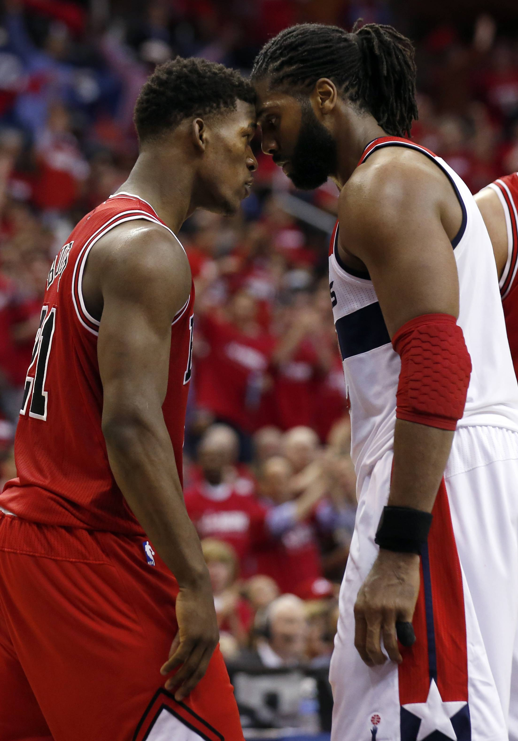 Chicago Bulls guard Jimmy Butler (21) and Washington Wizards forward Nene (42), from Brazil, stand head-to-head in the second half of Game 3 of an opening-round NBA basketball playoff series on Friday, April 25, 2014, in Washington. Nene received a double technical and was ejected. The Bulls won 100-97.