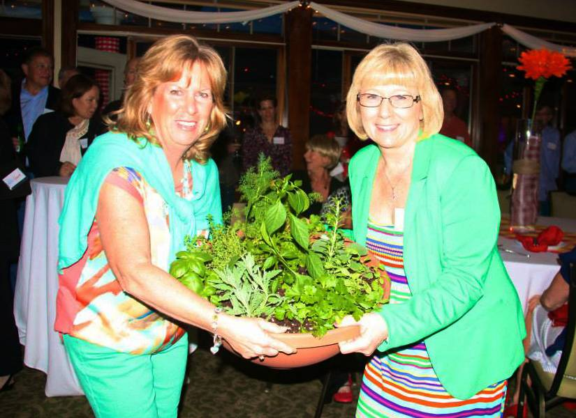 Mary Fremgen, left, presents Terri Pheanis with a plant in showing appreciation for Pheanis organizing the Backyard Barbecue fundraiser last year.