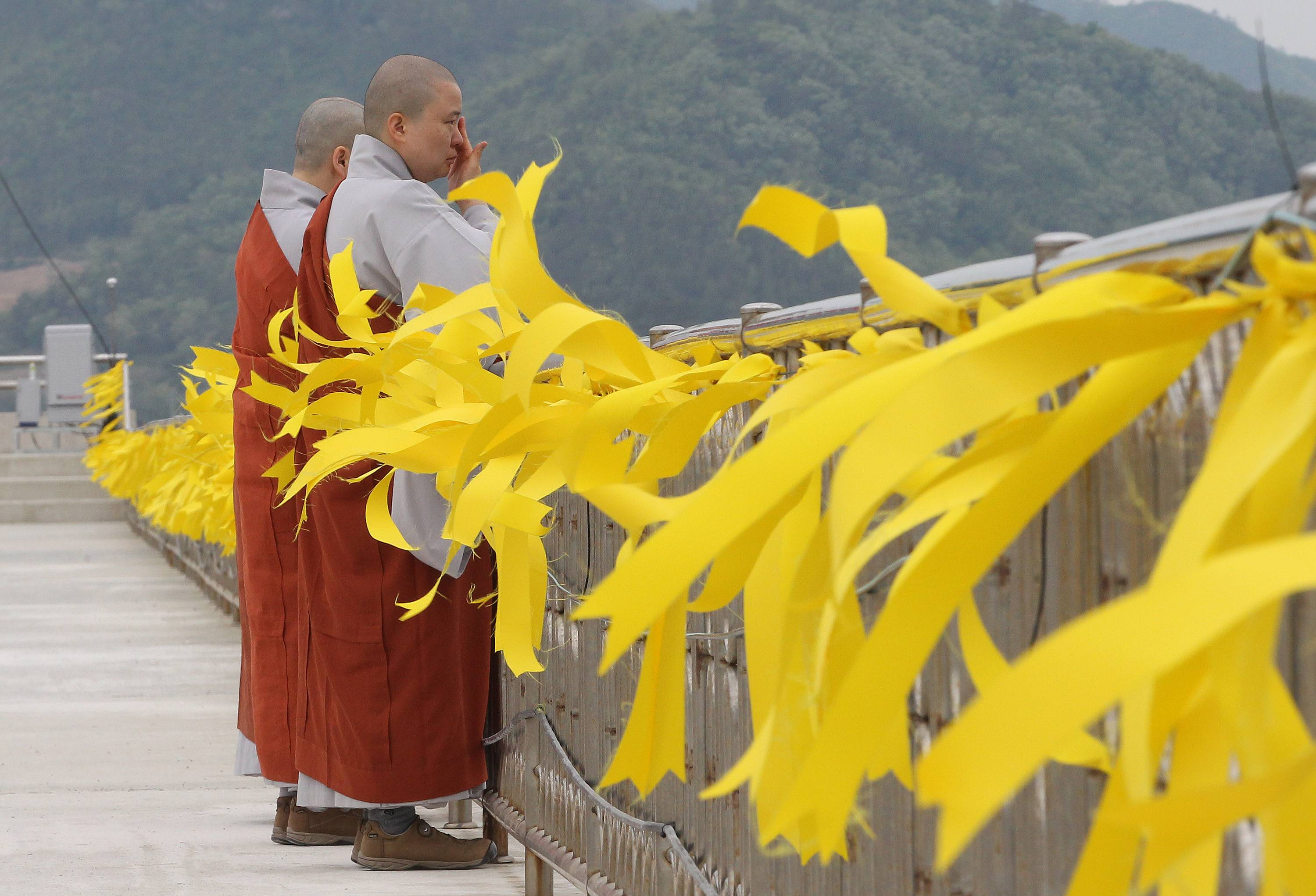 A Buddhist nun wipes her tears after attending a service as yellow ribbons are displayed as a sign of hope for the safe return of missing passengers of the sunken ferry Sewol at a port in Jindo, South Korea, Saturday, April 26, 2014. As visiting U.S. President Barack Obama offered South Koreans his condolences Friday for the ferry disaster in the water off the southern coast, the South Korean government conceded that some bodies have been misidentified and announced changes to prevent such mistakes from happening again. (AP Photo/Ahn Young-joon)