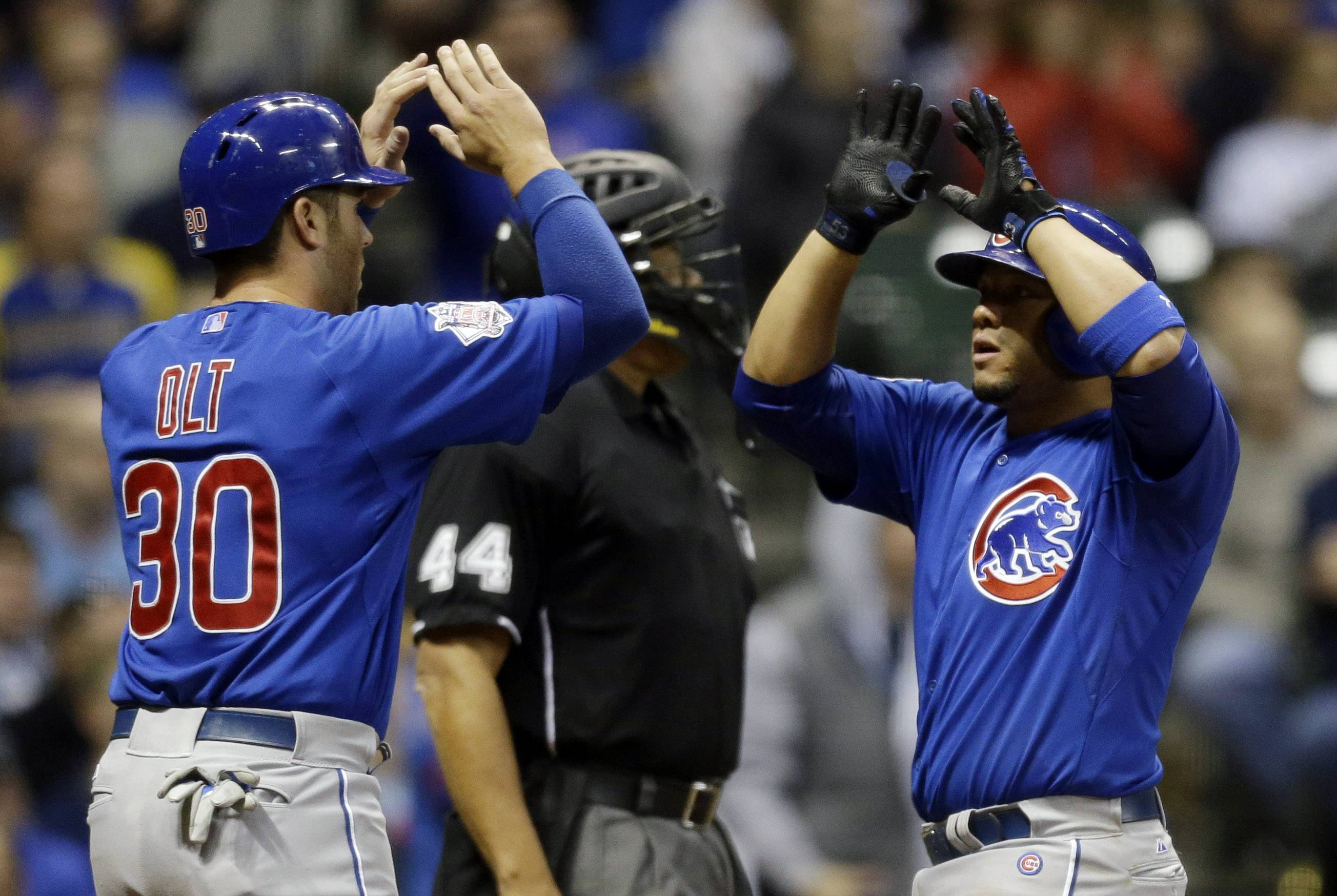 Chicago Cubs' Welington Castillo, right, gets high-fives from Mike Olt (30) after hitting a two-run home run against the Milwaukee Brewers during the eighth inning of a baseball game on Saturday, April 26, 2014, in Milwaukee.