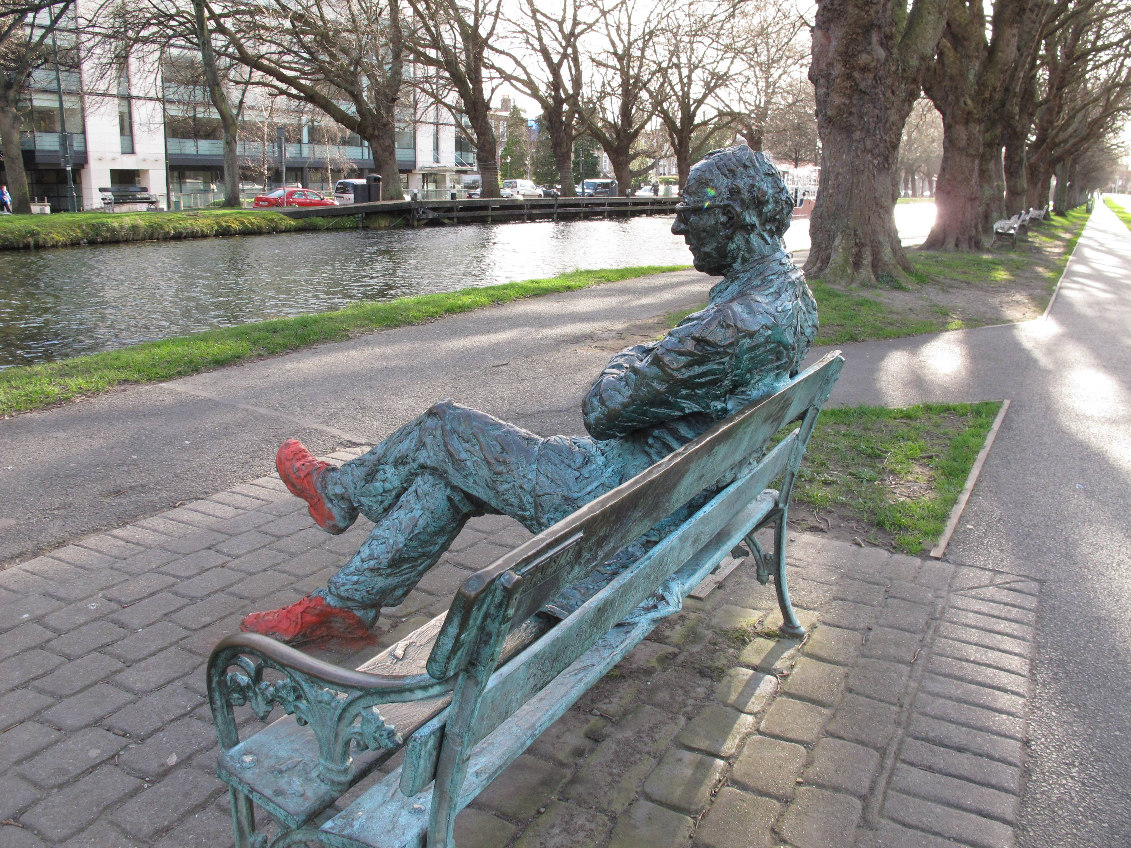 "A bronze depiction of poet Patrick Kavanagh sits by the Grand Canal in Dublin, Ireland. The statue was inspired by Kavanagh's poem about the canal: ""O commemorate me where there is water, canal water preferably, so stilly greeny at the heart of summer."""