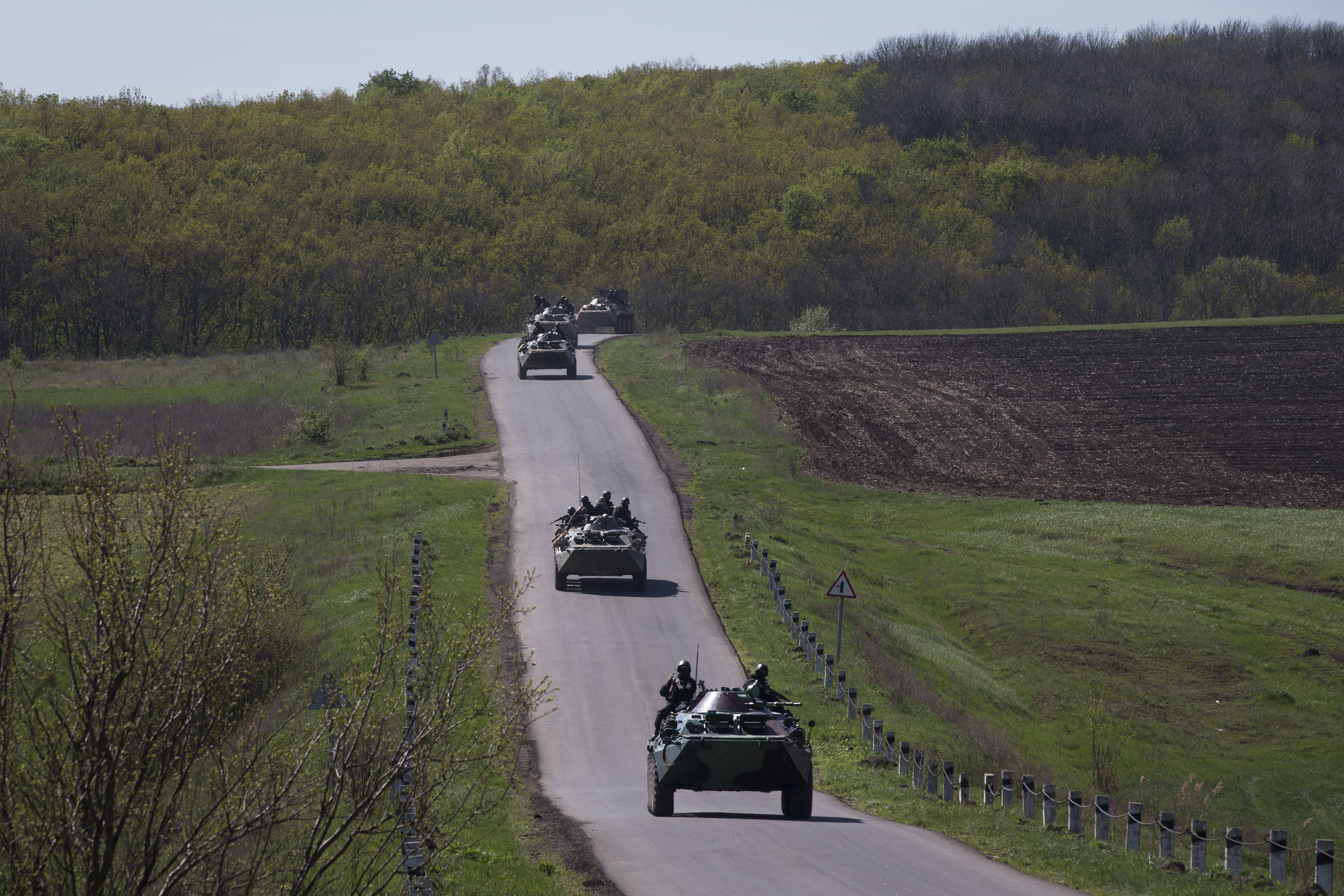 Ukrainian government troops atop of their armored personal carriers roll on a cou