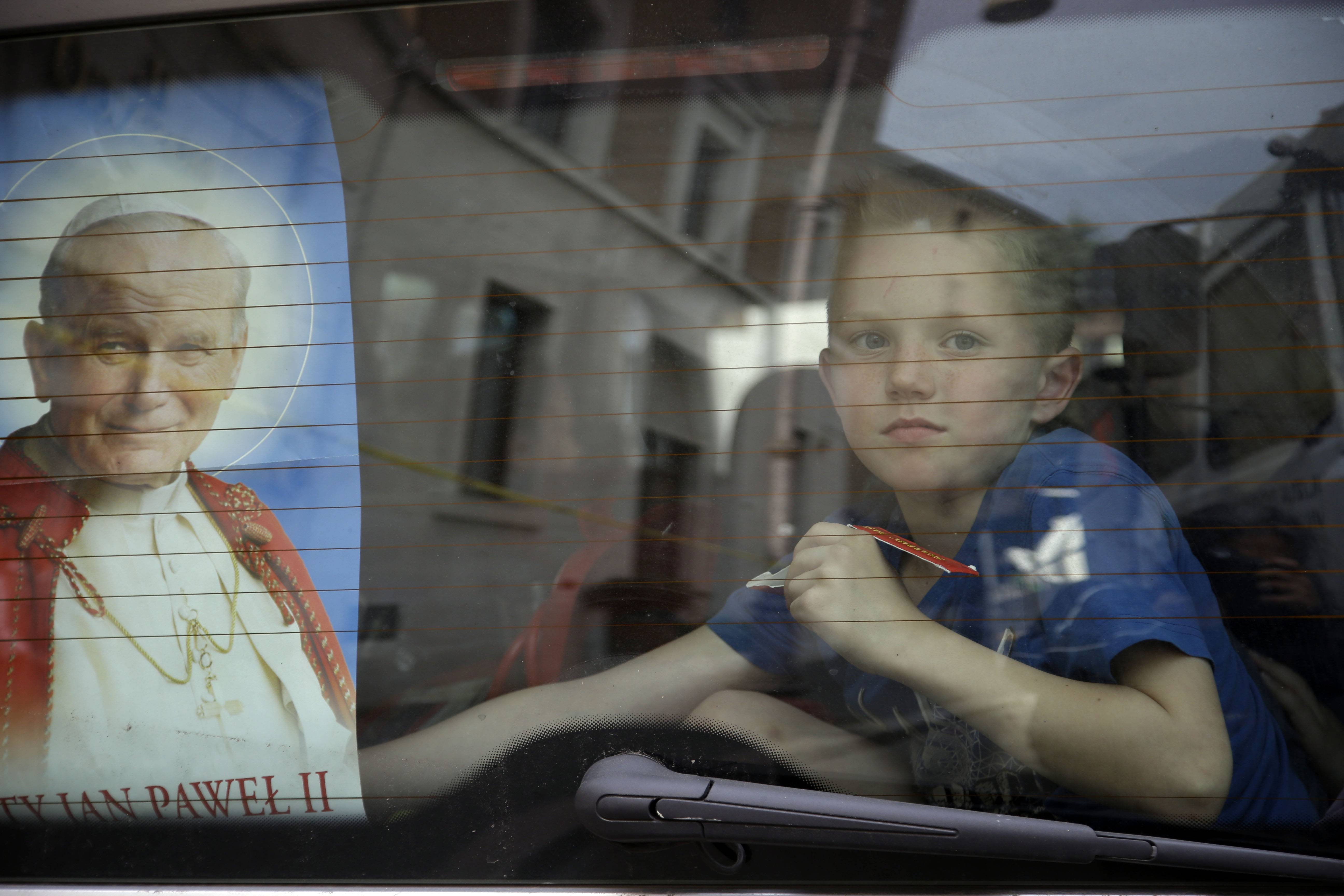 A child stand in the rear of a van adorned with a picture of late Pope John Paul II in Rome, Saturday. Hundred thousands of pilgrims and faithful are expected to reach Rome to attend the Sunday ceremony at the Vatican in which Pope Francis will elevate in a solemn ceremony John XXIII and John Paul II to sainthood.