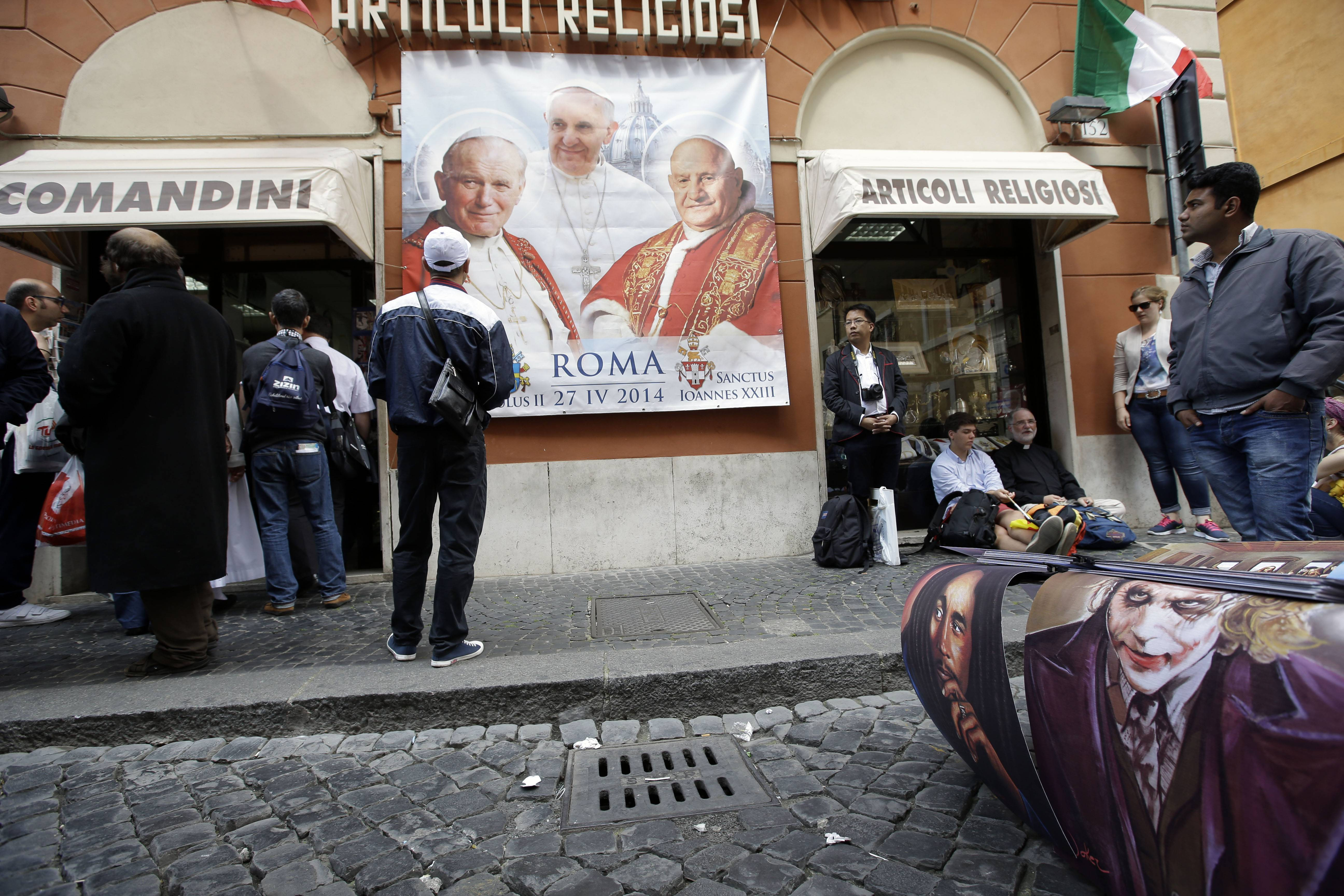 A street vendor stands near a shop selling religious items at Borgo Pio street near the Vatican, Saturday, April 26, 2014. Hundred thousands of pilgrims and faithful are expected to reach Rome to attend the scheduled April 27 ceremony at the Vatican in which Pope Francis will elevate in a solemn ceremony John XXIII and John Paul II to sainthood.