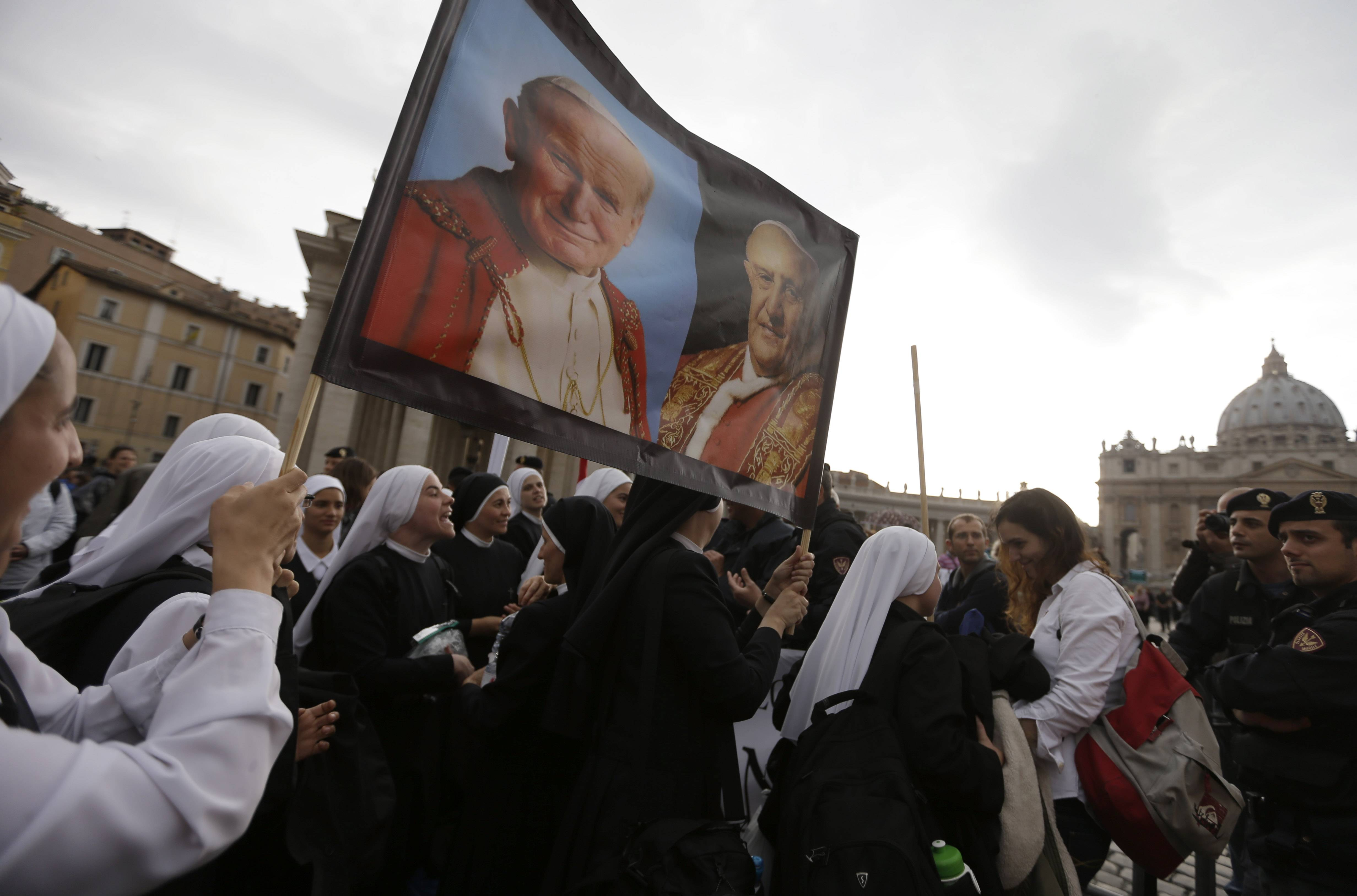 Nuns hold up pictures of late Pope John Paul II, top left, and Pope John XXIII, in St. Peter's Square at the Vatican, Saturday, April 26, 2014. Pilgrims and faithful are gathering in Rome to attend Sunday's ceremony at the Vatican where Pope Francis will elevate in a solemn ceremony John XXIII and John Paul II to sainthood.