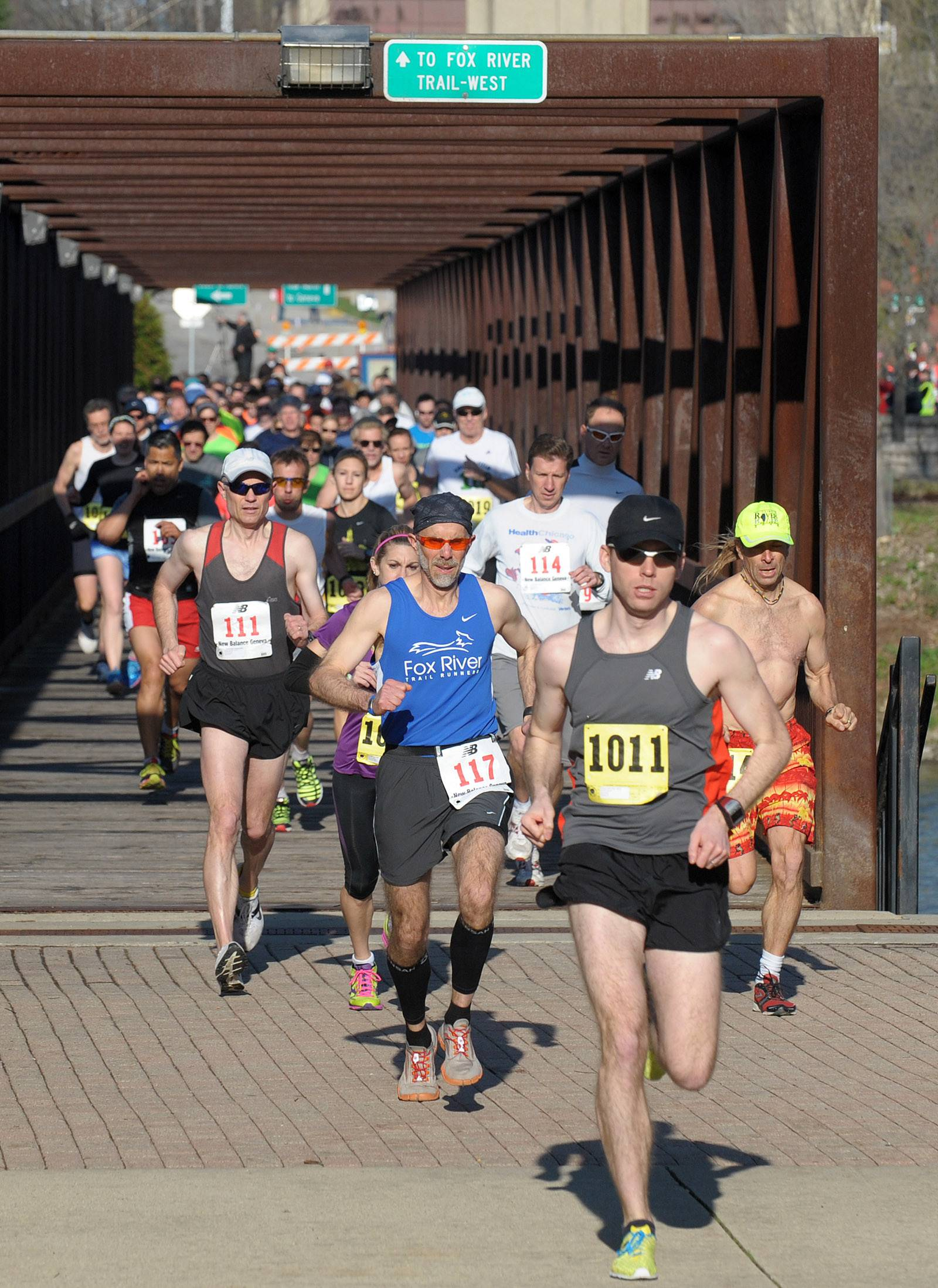 Runners take off across the Fox River on the pedestrian bridge for the Batavia Mothers' Club Foundation's 14th annual Fox Trot 5K/10K Saturday. This is the first year for the 10K. Tom Spadfora of Aurora (number 117) was the first runner to cross the finish line in the 5K.