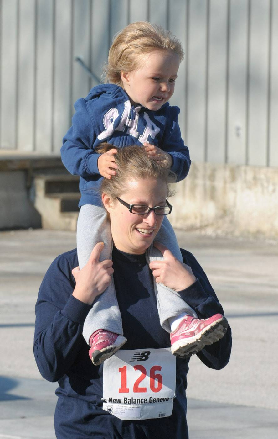 Becky Teusink of Batavia runs with her 2-year-old daughter, Kayleigh, on her shoulders in the Batavia Mothers' Club Foundation's 14th annual Fox Trot 5K Saturday. This is the first year she has run in the event.